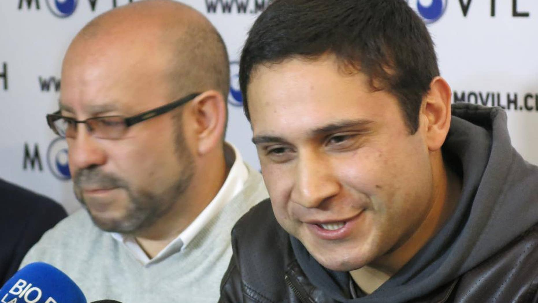 ADDS MONTH - Mauricio Ruiz, 24, sailor of the Chilean Navy, right, comes out publicly as gay during a press conference in Santiago, Chile, Wednesday Aug. 27, 2014. Ruiz who was accompanied by Rolando Jimenez, left, president of the Homosexual Liberation and Integration Movement, is the first member of the Chilean armed forces ever to come out publicly as gay with the approval of the High Command of the Chilean navy. (AP Photo/Eva Vergara)