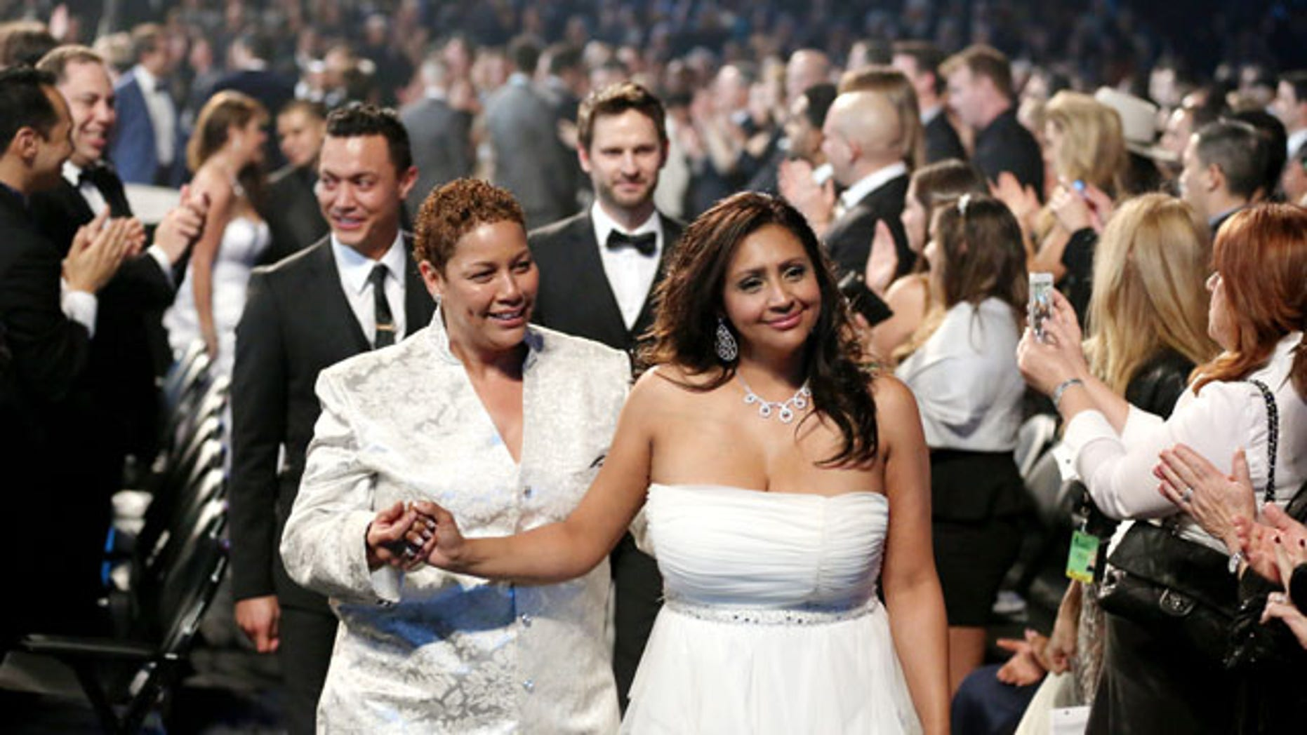"January 26, 2014: Audience members participate in a same sex wedding during a performance of ""Same Love"" by Macklemore and Ryan Lewis at the 56th annual Grammy Awards at Staples Center in Los Angeles. With Queen Latifah presiding from the stage and the music playing, 33 straight and gay couples lined the aisle dressed in wedding finery. Under Latifah's command, they exchanged rings near the end of Sunday night's show televised on CBS. (Photo by Matt Sayles/Invision/AP)"