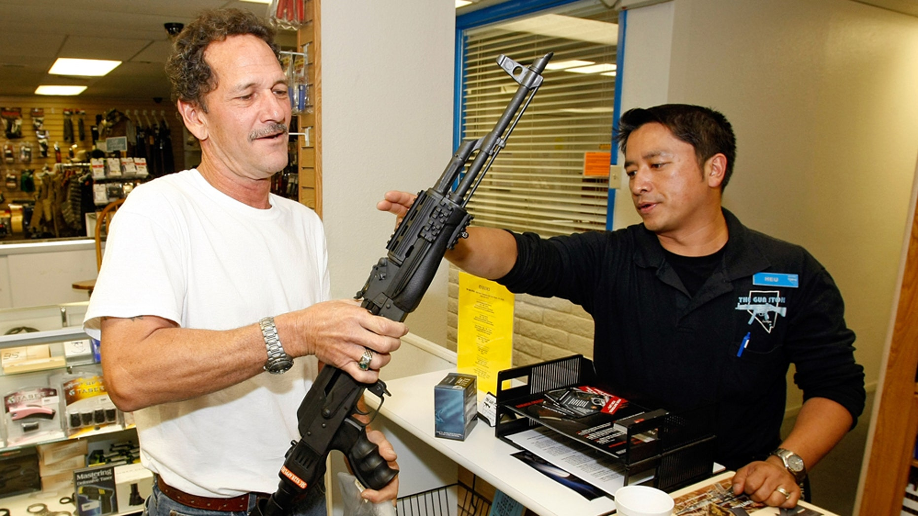 LAS VEGAS - NOVEMBER 14:  The Gun Store rangemaster Heu Thao (R) shows Gregory Smith of Nevada the modifications made to his AK-47 assault rifle November 14, 2008 in Las Vegas, Nevada. Store manager Cliff Wilson said he's seen a large spike in sales since Barack Obama was elected president on November 4, with customers citing fears about the president-elect's record on firearms. The election, combined with a slumping economy, has contributed to an overall increase of 25-30 percent in gun sales at the store, Wilson said.  (Photo by Ethan Miller/Getty Images)