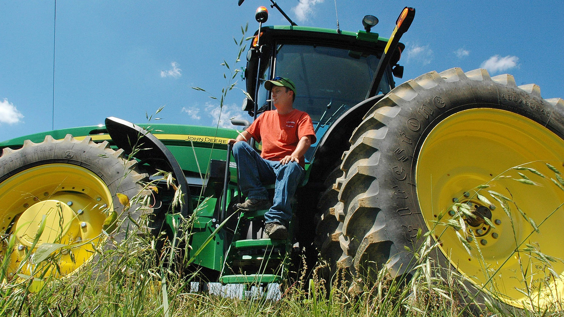In a Thursday, May 10, 2012 photo, tomato farmer Keith Dickie sits on a tractor at his farm near Oneonta, Ala. (AP Photo/Jay Reeves)