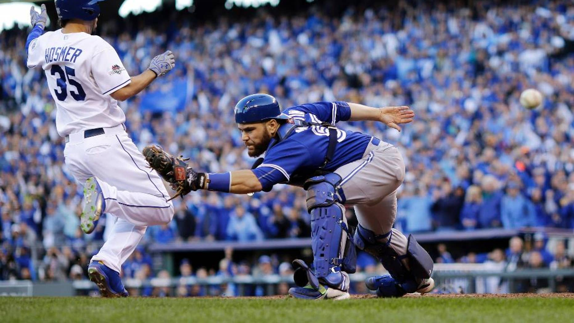 Toronto Blue Jays catcher Russell Martin misses the throw to home plate as Kansas City Royals' Eric Hosmer, right, comes in to score during the seventh inning in Game 2 of baseball's American League Championship Series, Saturday, Oct. 17, 2015, in Kansas City, Mo.  (AP Photo/Matt Slocum)