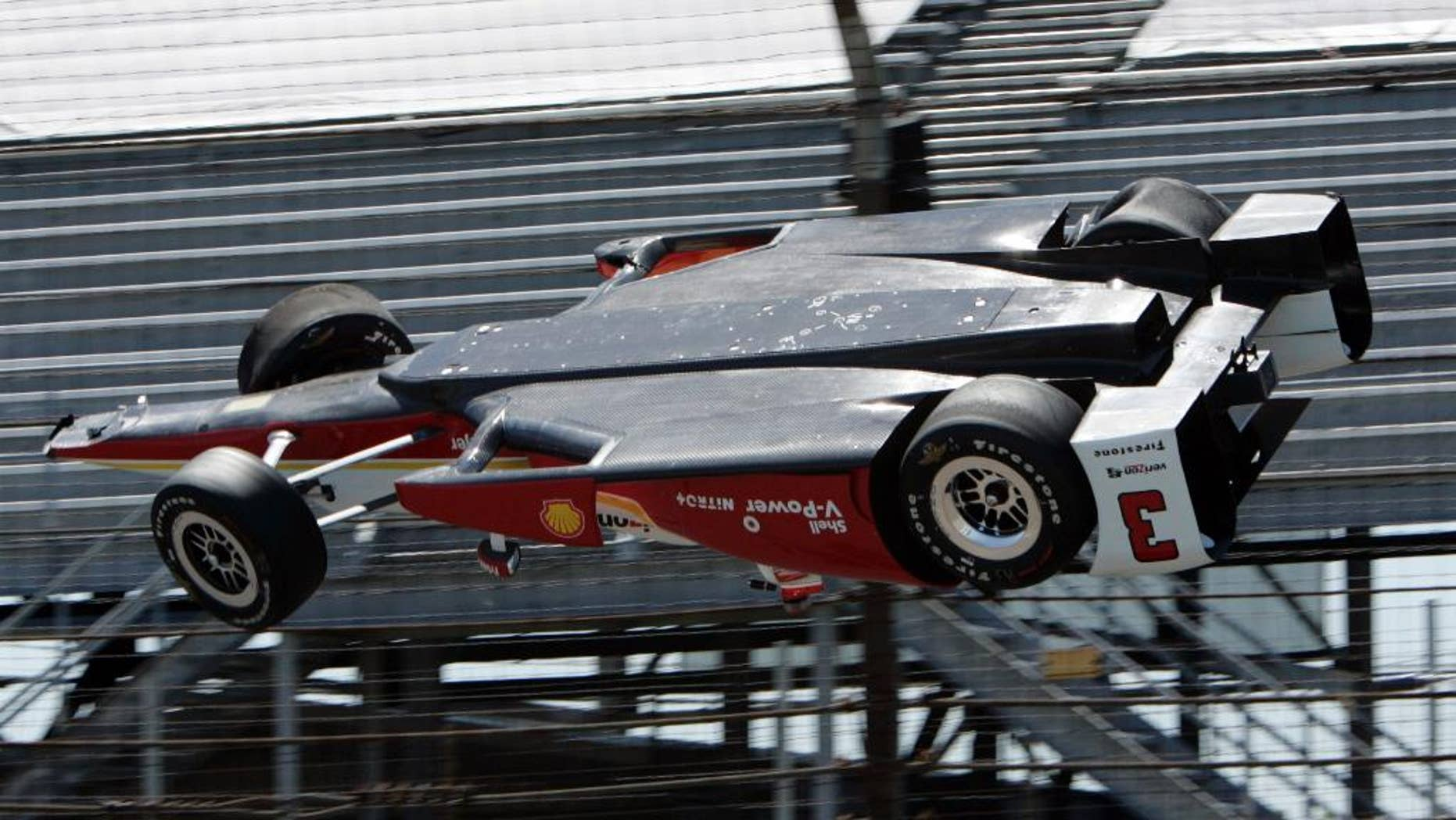 AP10ThingsToSee - The car driven by Helio Castroneves, of Brazil, is airborne after hitting a wall in the first turn during practice for the Indianapolis 500 auto race at Indianapolis Motor Speedway in Indianapolis on Wednesday, May 13, 2015. The car landed upside down before rolling onto its wheels but Castroneves was not seriously hurt. (AP Photo/Joe Watts)