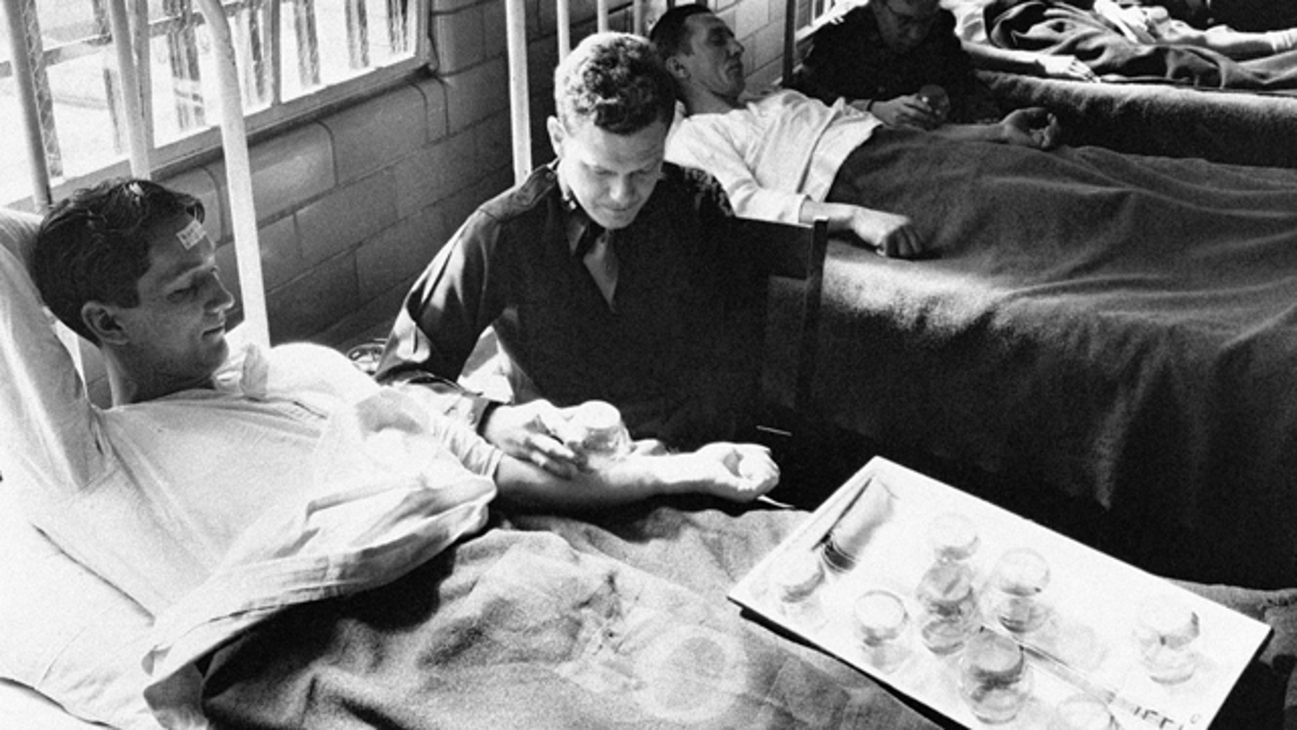 In this June 25, 1945 picture, army doctors expose patients to malaria-carrying mosquitoes in the malaria ward at Stateville Penitentiary in Crest Hill, Ill.