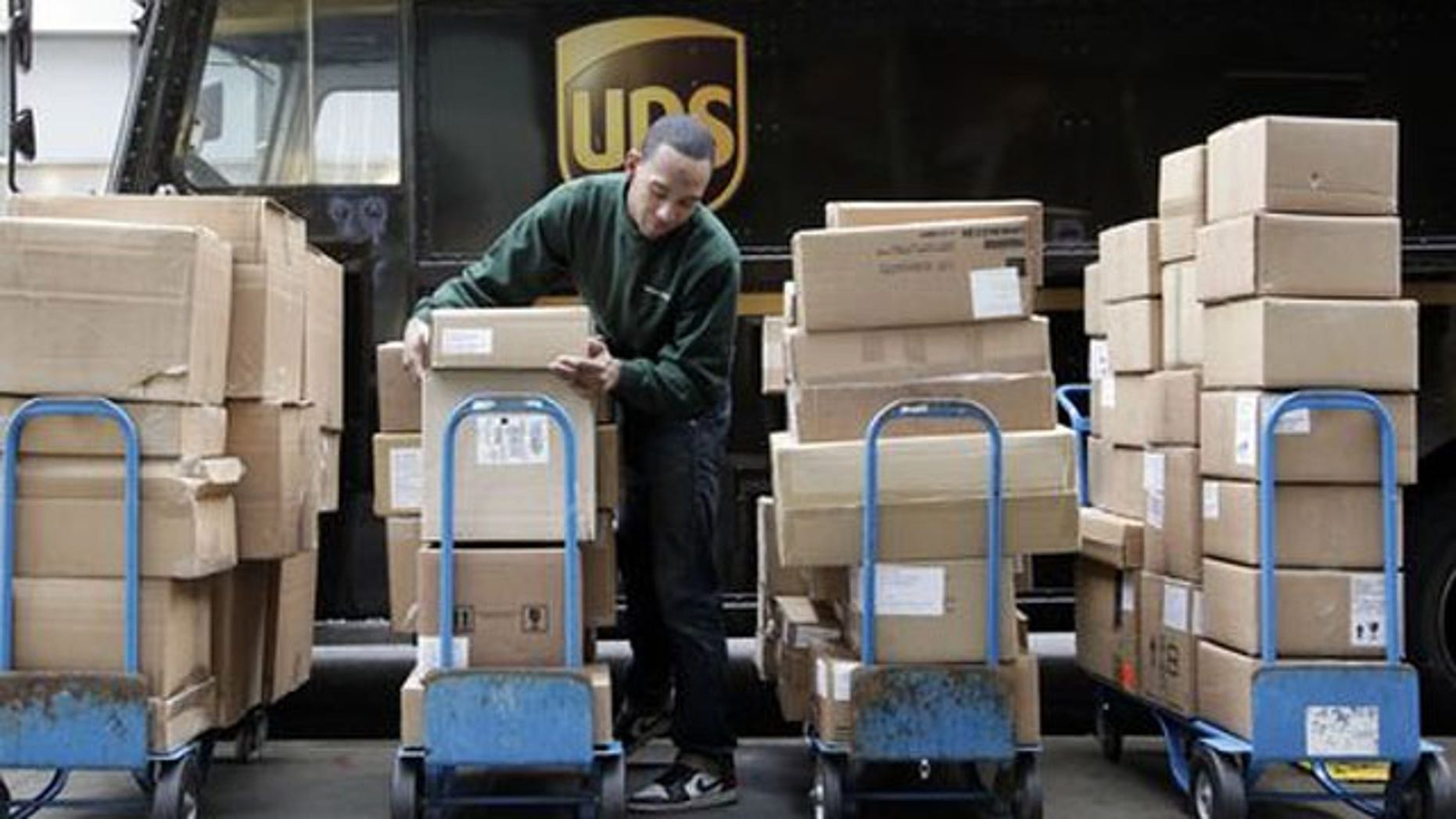 FILE- A UPS driver unloads packages from a truck (AP/FILE)