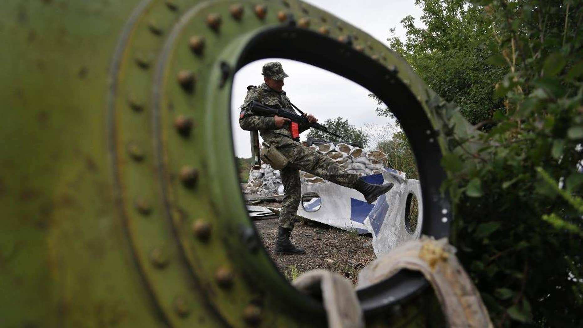 """AP10ThingsToSee- A Pro-Russian rebel looks at pieces of the Malaysia Airlines Flight 17 plane near village of Rozsypne, eastern Ukraine, Tuesday, Sept. 9, 2014. The Dutch team investigating the downing of Malaysia Airlines Flight 17 over Eastern Ukraine says the crash was likely caused by the plane being hit by multiple """"high-energy objects from outside the aircraft."""" (AP Photo/Sergei Grits)"""