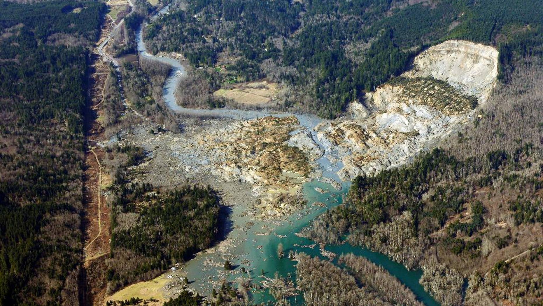 AP10ThingsToSee  - This aerial photo taken Monday, March 24, 2014 shows the massive mudslide that killed at least eight people Saturday and left dozens missing, near Arlington, Wash. (AP Photo/Ted S. Warren, File)