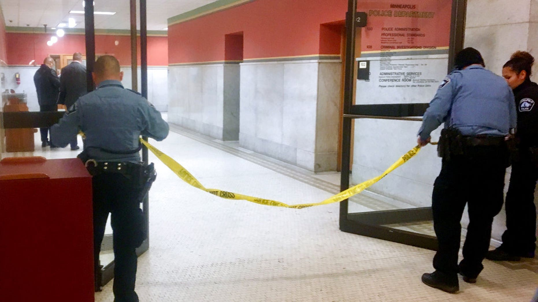 Police set up crime scene tape outside a Minneapolis police room at Minneapolis City Hall on Monday, Dec. 18, 2017. Minneapolis police say their officers have been involved in a shooting inside the department's investigative unit at City Hall. (AP Photo/Jeff Baenen)