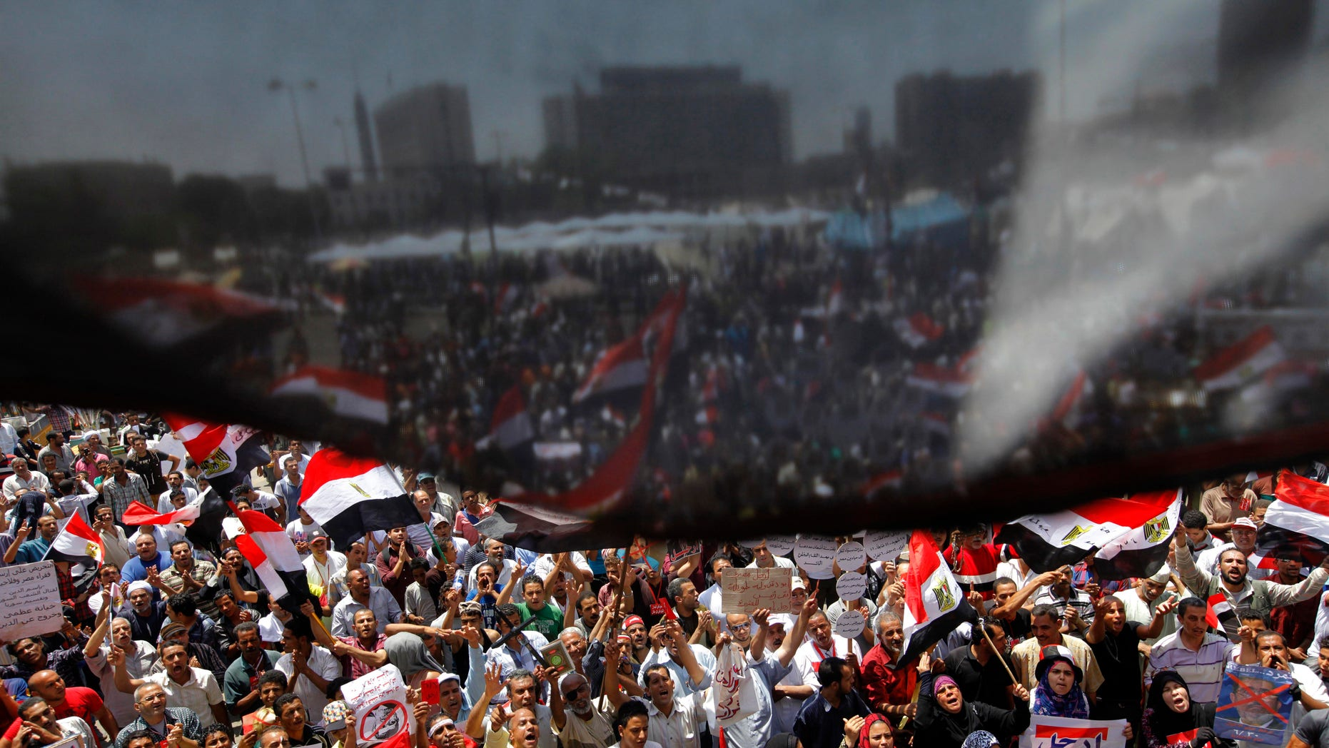 Opponents of Egypt's Islamist President Mohammed Morsi wave national flags as they demonstrate in Tahrir Square in Cairo, Egypt, Friday, June 28, 2013. (AP Photo/Amr Nabil)
