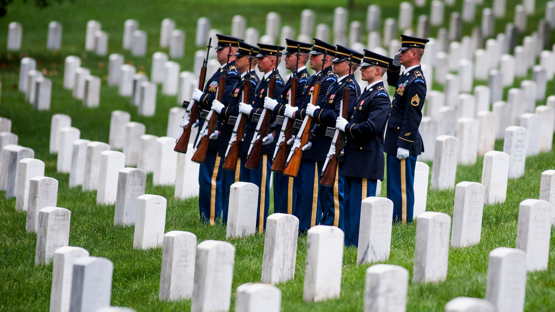 In this May 29, 2014 file photo, a firing party stands at attention during burial services at Arlington National Cemetery in Arlington, Va.