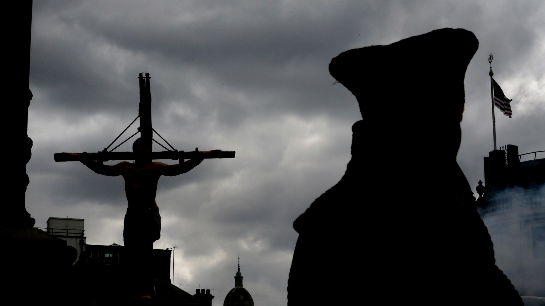 An actor is silhouetted hanging on a cross during a performance in Trafalgar Square in London, Friday, April 18, 2014. The play called 'The Passion of Jesus' was a free performance depicting the betrayal, capture, trial, crucifixion and resurrection of Jesus, performed by the Wintershall players. (AP Photo/Kirsty Wigglesworth)