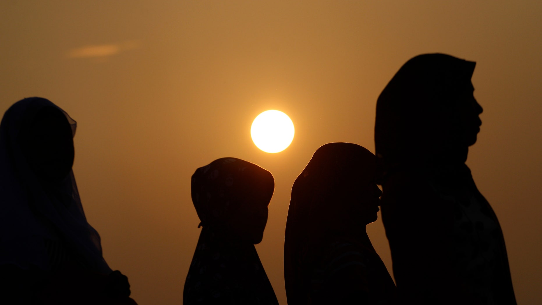 Indonesian Muslim women walk before Eid al-Fitr prayer that marks the end of the holy fasting month of Ramadan  in Jakarta, Indonesia, Thursday, Aug. 8, 2013. (AP Photo/Achmad Ibrahim)