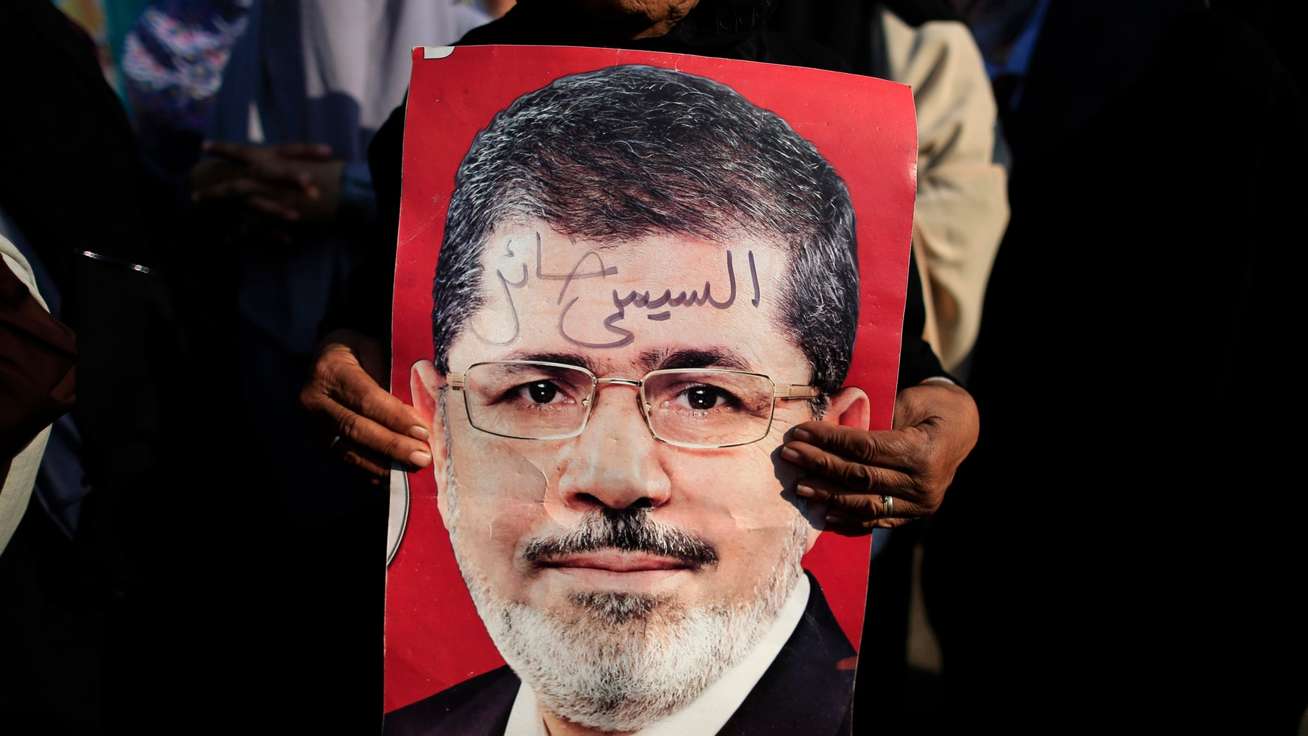 """A supporter holds a poster of Egypt's Islamist President Mohammed Morsi with Arabic that reads, """"Sisi traitor,"""" during a rally, in Nasser City, Cairo, Egypt, July 4, 2013."""