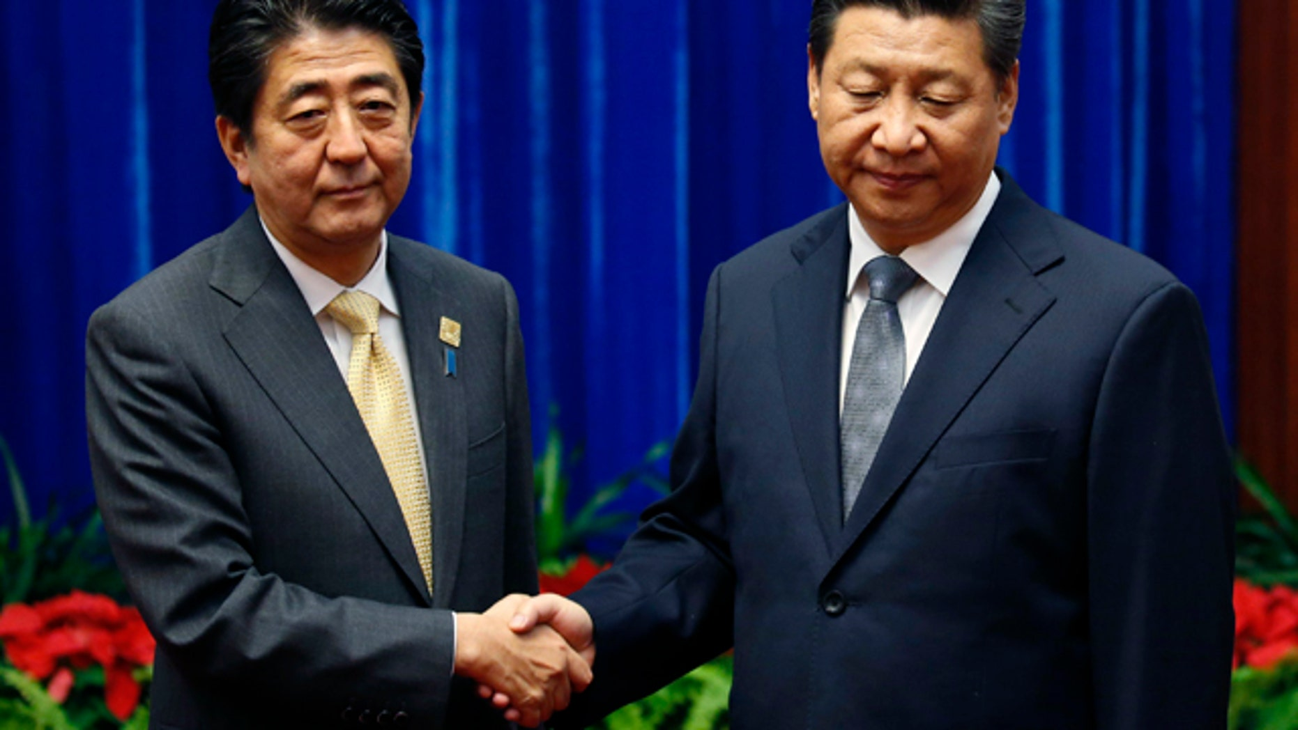 November 10, 2014: China's President Xi Jinping, right,  shakes hands with Japan's Prime Minister Shinzo Abe, during their meeting at the Great Hall of the People, on the sidelines of the Asia Pacific Economic Cooperation (APEC) meetings, in Beijing.  (AP Photo/Kim Kyung-Hoon, Pool)