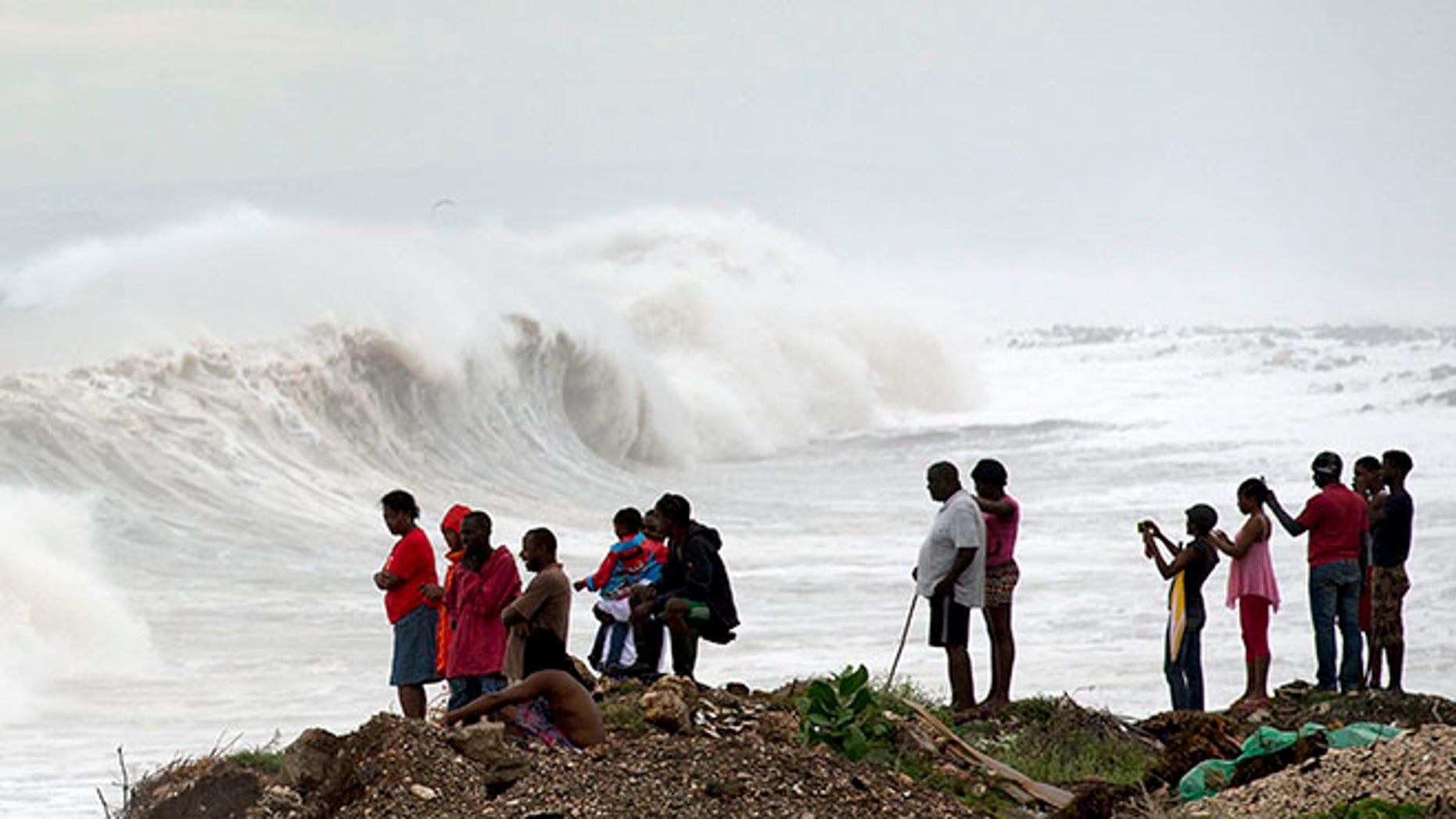 People stand on the coast watching the surf produced by Hurricane Matthew, on the outskirts of Kingston, Jamaica, Monday, Oct. 3, 2016.