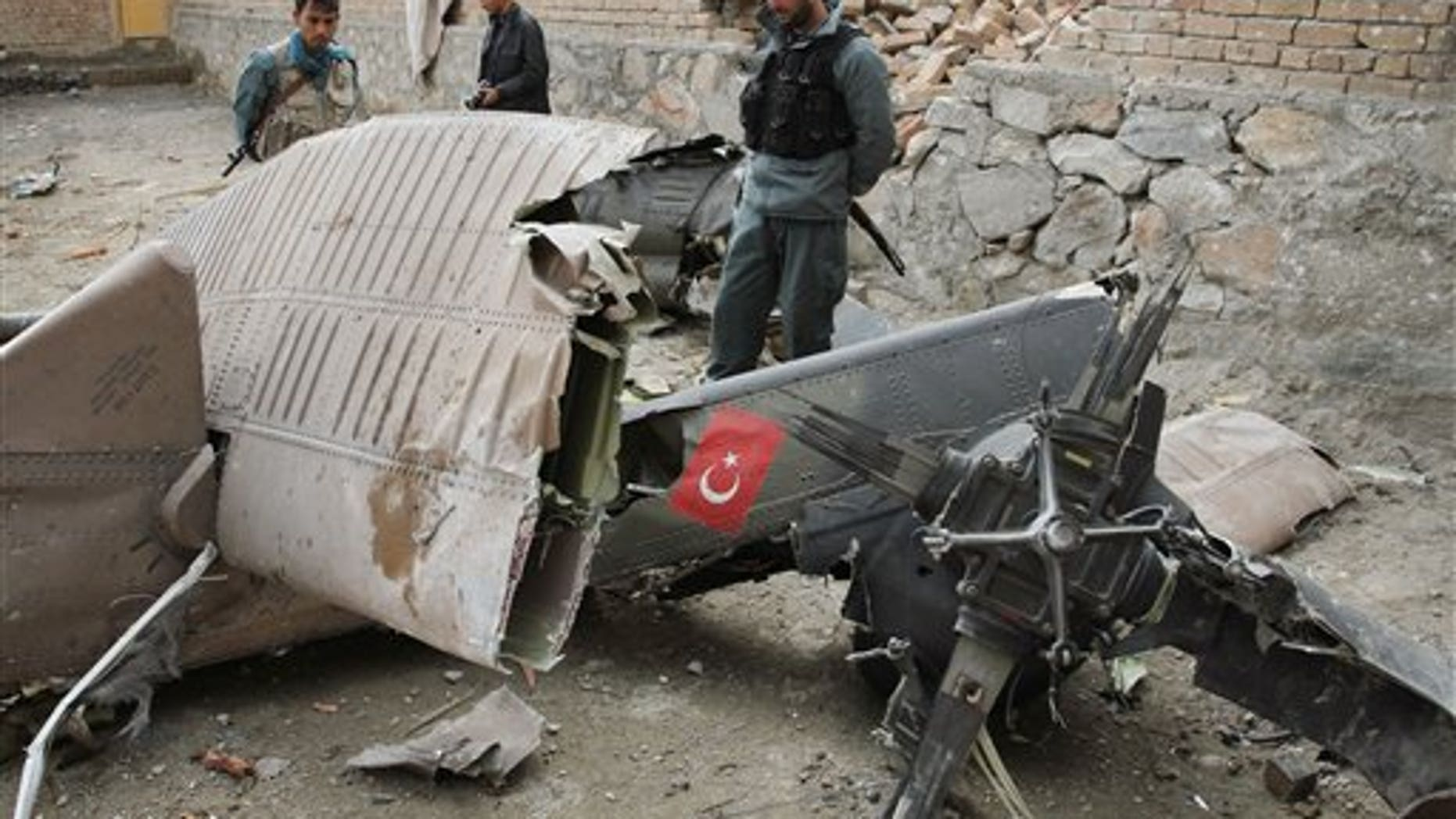 March 16, 2012: An Afghan policemen looks at the wreckage from a crashed Turkish helicopter on the outskirts of Kabul.