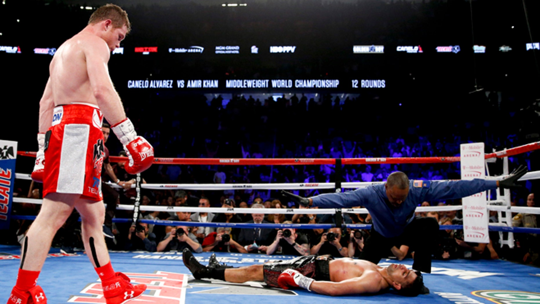 Canelo Alvarez, left, watches after knocking down Amir Khan during their WBC middleweight title fight Saturday, May 7, 2016, in Las Vegas. (AP Photo/John Locher)