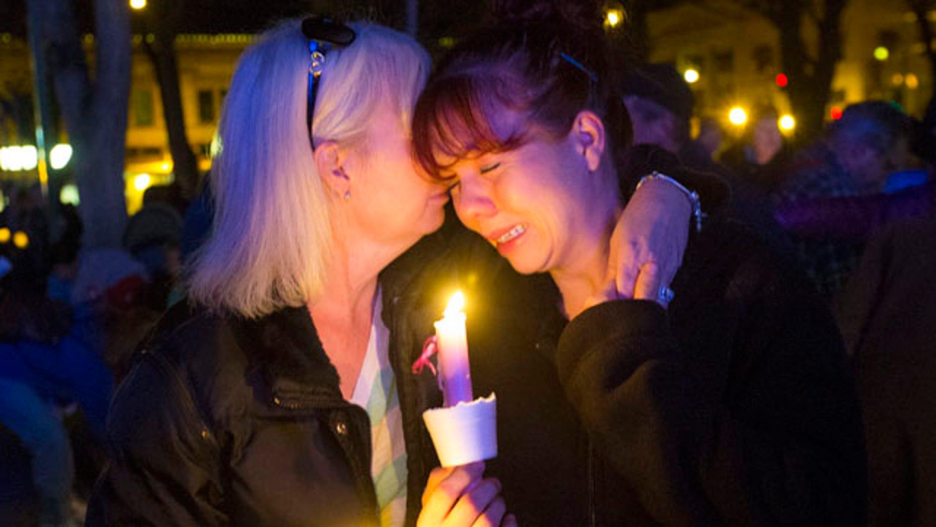 Feb. 18, 2015: Tonya Castillo, left, comforts her daughter Tiffany Reid during a candlelight memorial for Kayla Mueller in Prescott, Ariz. (AP Photo/The Arizona Republic, Michael Chow)