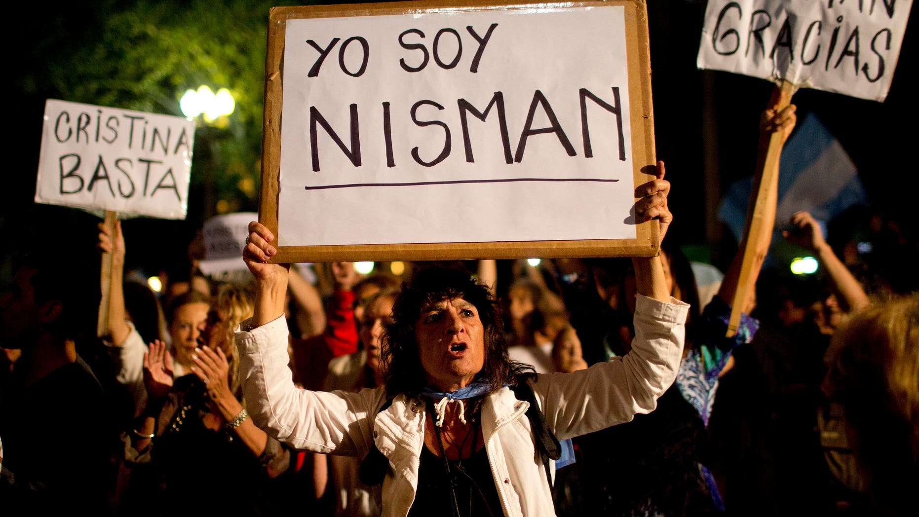 """A demonstrator holds a sign that reads in Spanish """"I am Nisman"""" during a protest sparked by the death of special prosecutor Alberto Nisman, outside the government house in Plaza de Mayo in Buenos Aires, Argentina, Monday, Jan. 19, 2015. The other signs read """"Enough Cristina,"""" left, and """"Thank you Nisman."""" Nisman, who had been investigating the 1994 bombing of the AMIA Jewish community center in Buenos Aires that killed 85 people and who accused President Cristina Fernandez of shielding Iranian suspects, was found dead with a gunshot to his head in the bathroom of his apartment late Sunday, hours before he was to testify in a Congressional hearing about the case. (AP Photo/Rodrigo Abd)"""