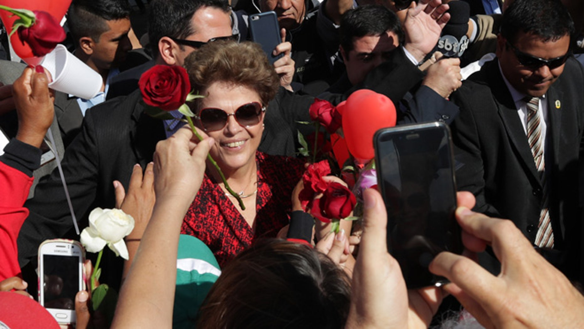 Brazil's impeached President Dilma Rousseff receives flowers from supporters as she leaves the presidential residence, on Sept. 6, 2016.
