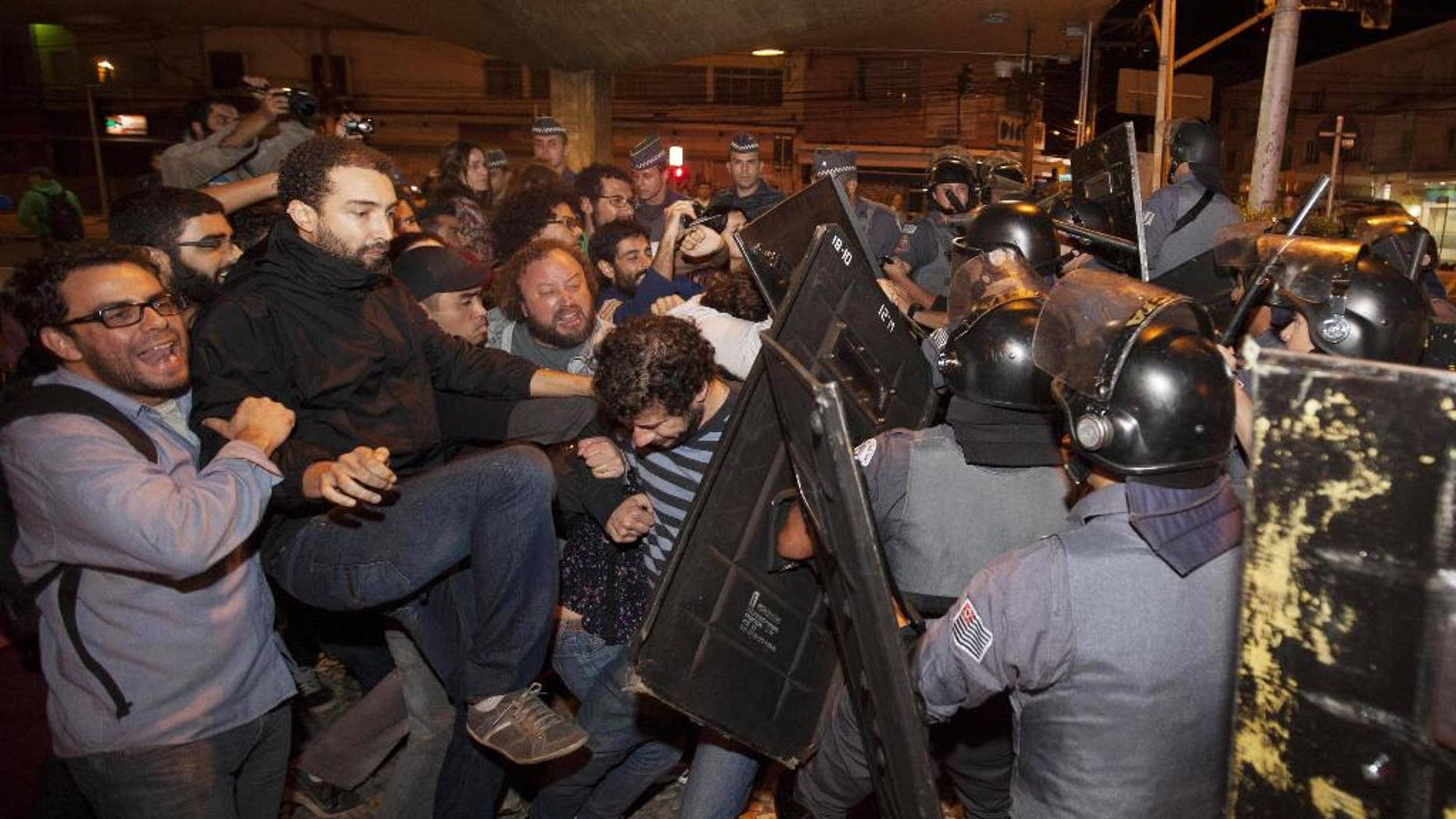 Subway train operators, along with activists from social movements, clash with riot police in front of the Ana Rosa metro station, in an ongoing subway strike, in Sao Paulo, Brazil, Monday, June 9, 2014. Authorities are deeply worried about the strike because the subway is the main means of transportation for World Cup fans scheduled to attend Thursday's opening match when Brazil takes on Croatia. The stadium is about 20 kilometers (12 miles) east of central Sao Paulo, where most tourists stay. (AP Photo/Mario Angelo)