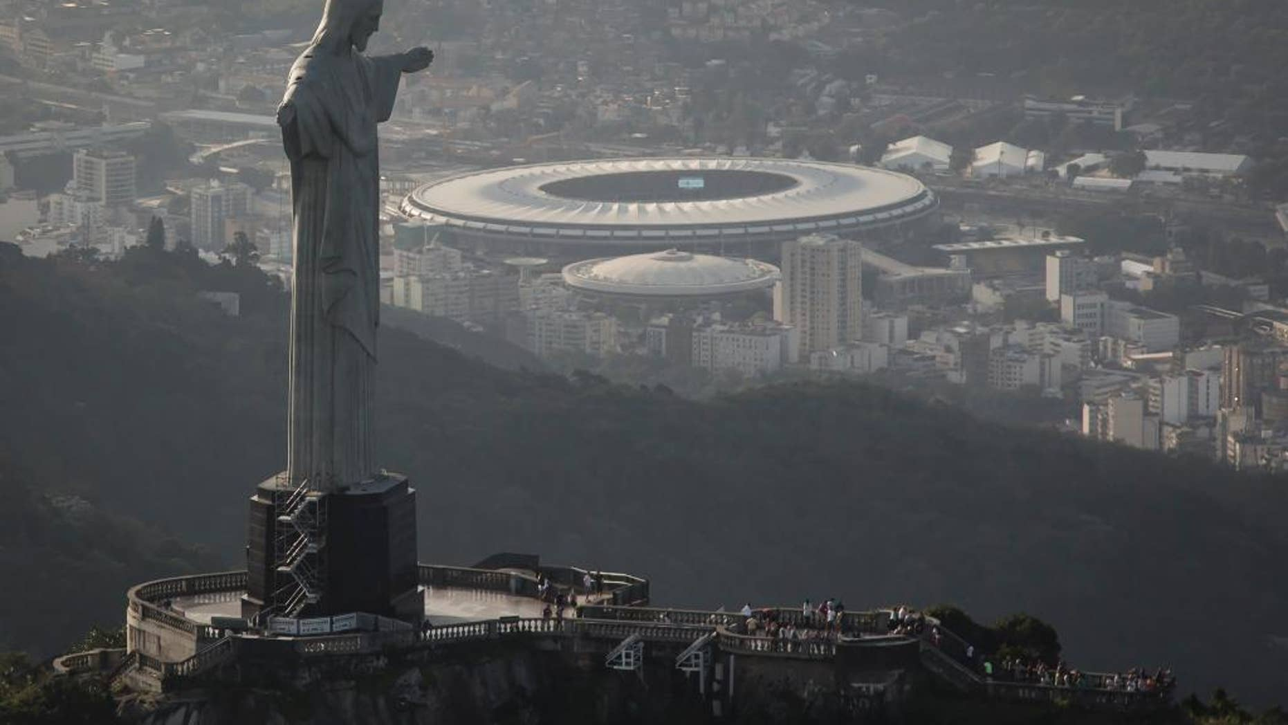 This aerial view shot through an airplane window shows the Maracana stadium behind the Christ the Redeemer statue in Rio de Janeiro, Brazil, Tuesday, May 13, 2014. As opening day for the World Cup approaches, people continue to stage protests, some about the billions of dollars spent on the World Cup at a time of social hardship, but soccer is still a unifying force. The international soccer tournament will be the first in the South American nation since 1950. (AP Photo/Felipe Dana)