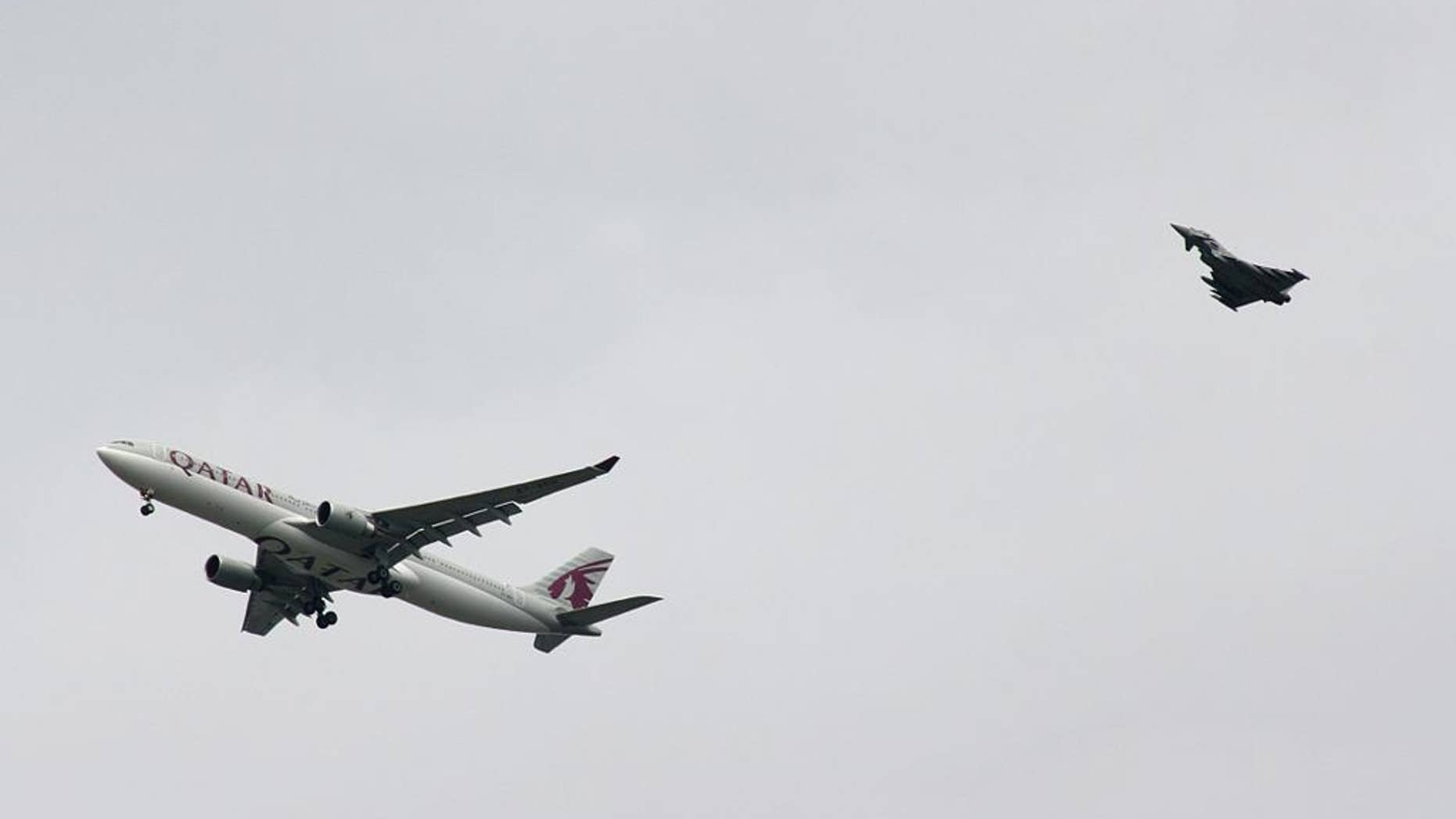A military fighter jet escorts a passenger jet as it comes in to land at Manchester airport, Manchester, England, Tuesday, Aug. 5, 2014. Police say they have arrested a man on suspicion of making a hoax bomb threat after Qatar Airways Flight 23 landed with a military fighter escort at Britain's Manchester Airport. (AP Photo/Matthew Cossar)