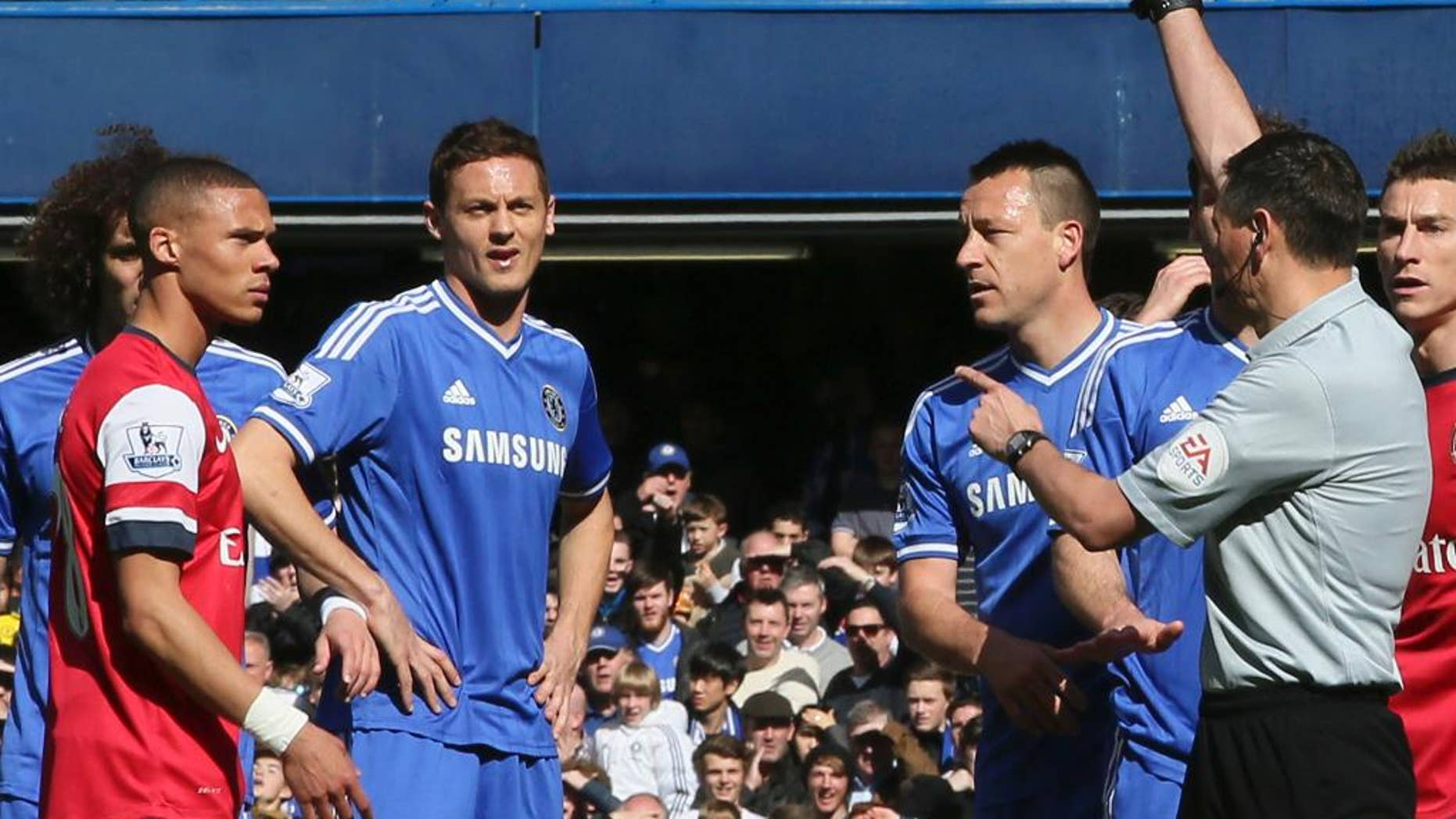 Referee Andre Marriner, in grey, sends off Arsenal's Kieran Gibbs, left, during their English Premier League soccer match between Chelsea and Arsenal at Stamford Bridge stadium in London Saturday, Mar  22  2014. (AP Photo/Alastair Grant)