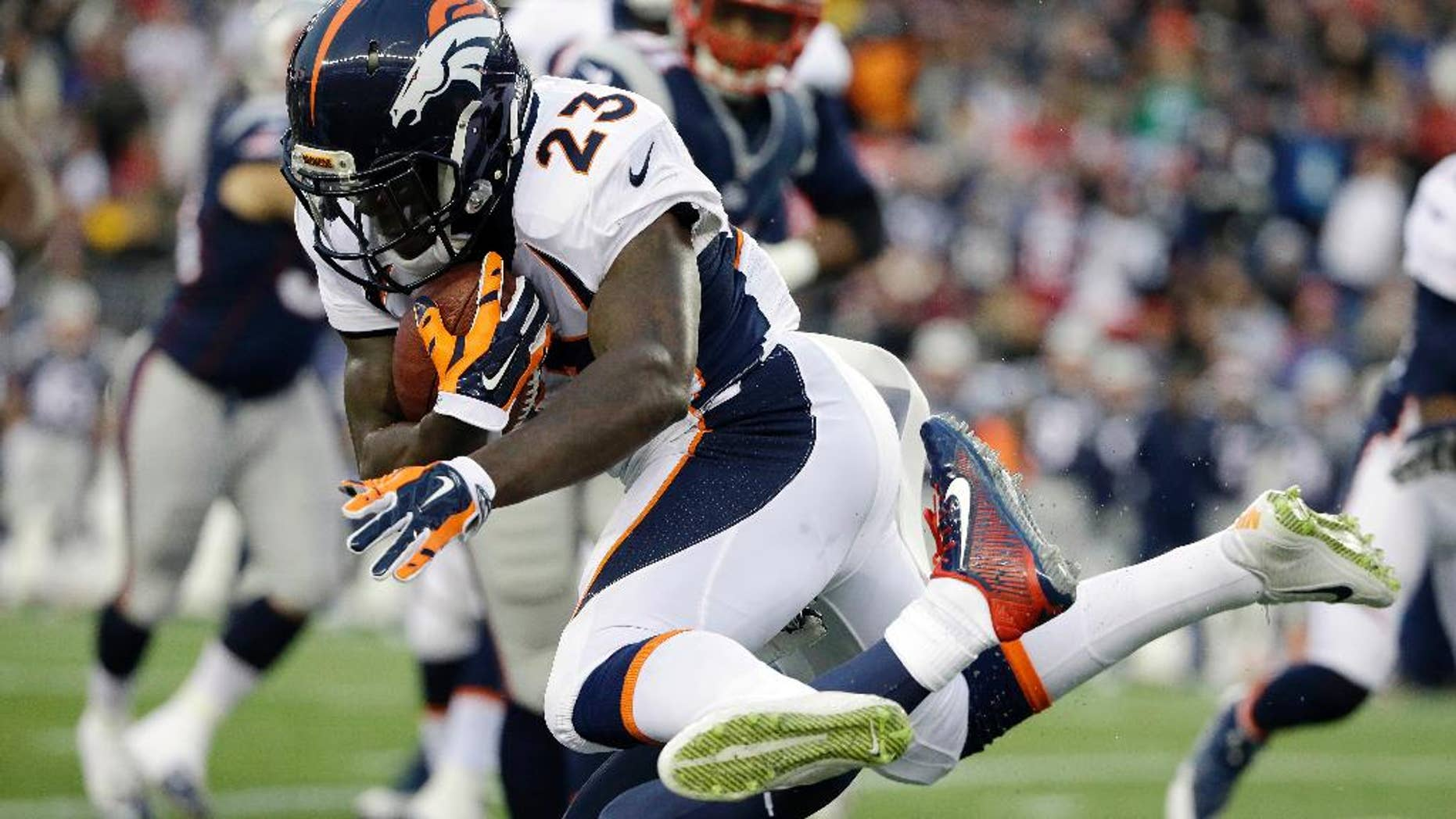 Denver Broncos running back Ronnie Hillman (23) leaps over a New England Patriots defender in the first half of an NFL football game on Sunday, Nov. 2, 2014, in Foxborough, Mass. (AP Photo/Steven Senne)
