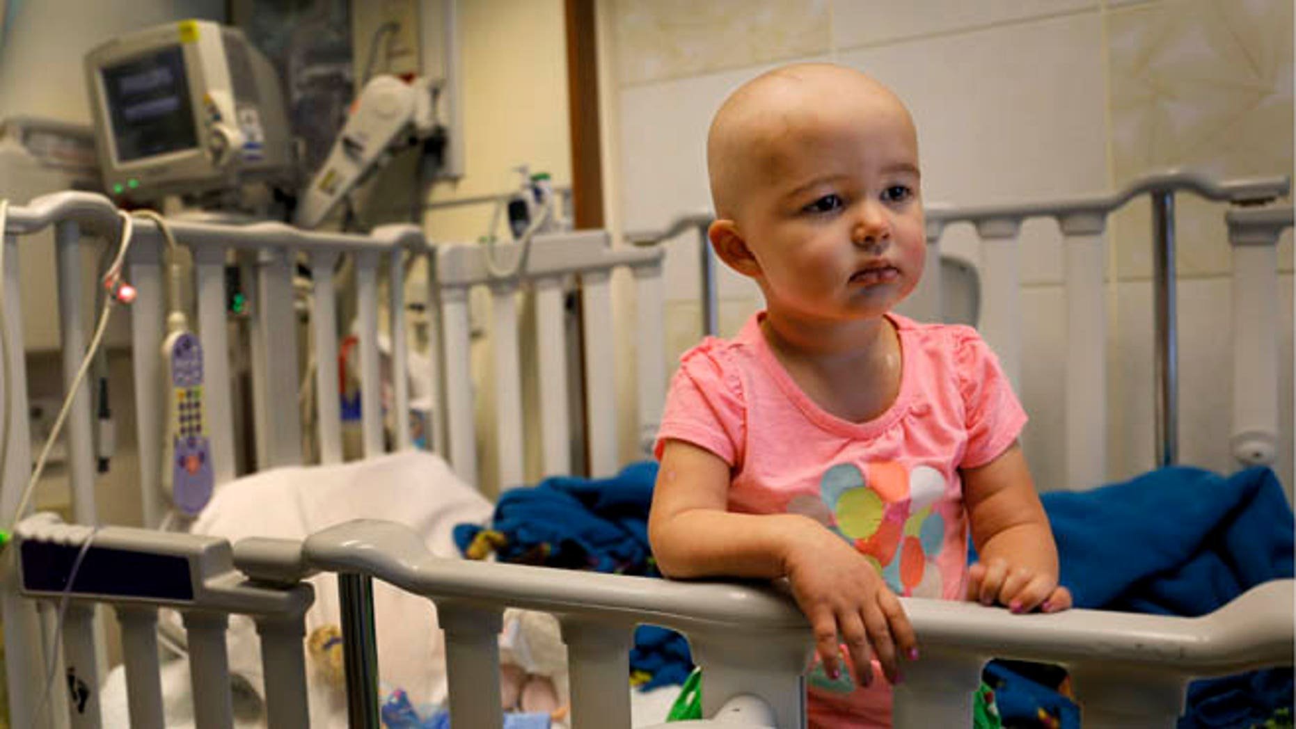 In this June 11, 2015 photo,Talia Pisano stands in her bed at Lurie Children's Hospital in Chicago. Talia is getting tough treatment for kidney cancer that spread to her brain. She's also getting a chance at having babies of her own someday. To battle infertility sometimes caused by cancer treatment, some childrenâs hospitals are trying a futuristic approach: removing and freezing immature ovary and testes tissue, with hopes of being able to put it back when patients reach adulthood and want to start families. (AP Photo/Christian K. Lee)