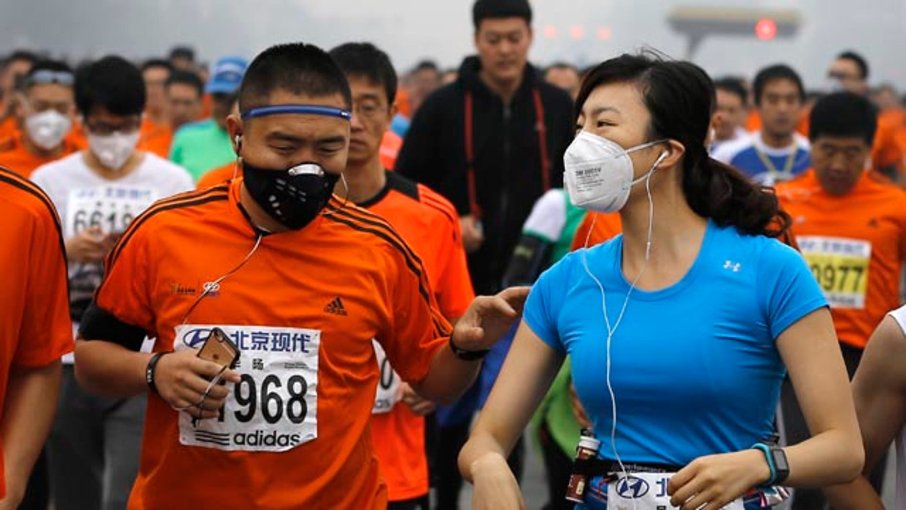 October 19, 2014: Runners wearing masks to protect themselves from pollutants jog past Chang'an Avenue near Tiananmen Square shrouded in haze while taking part in the 2014 Beijing International Marathon. (AP Photo/Andy Wong)