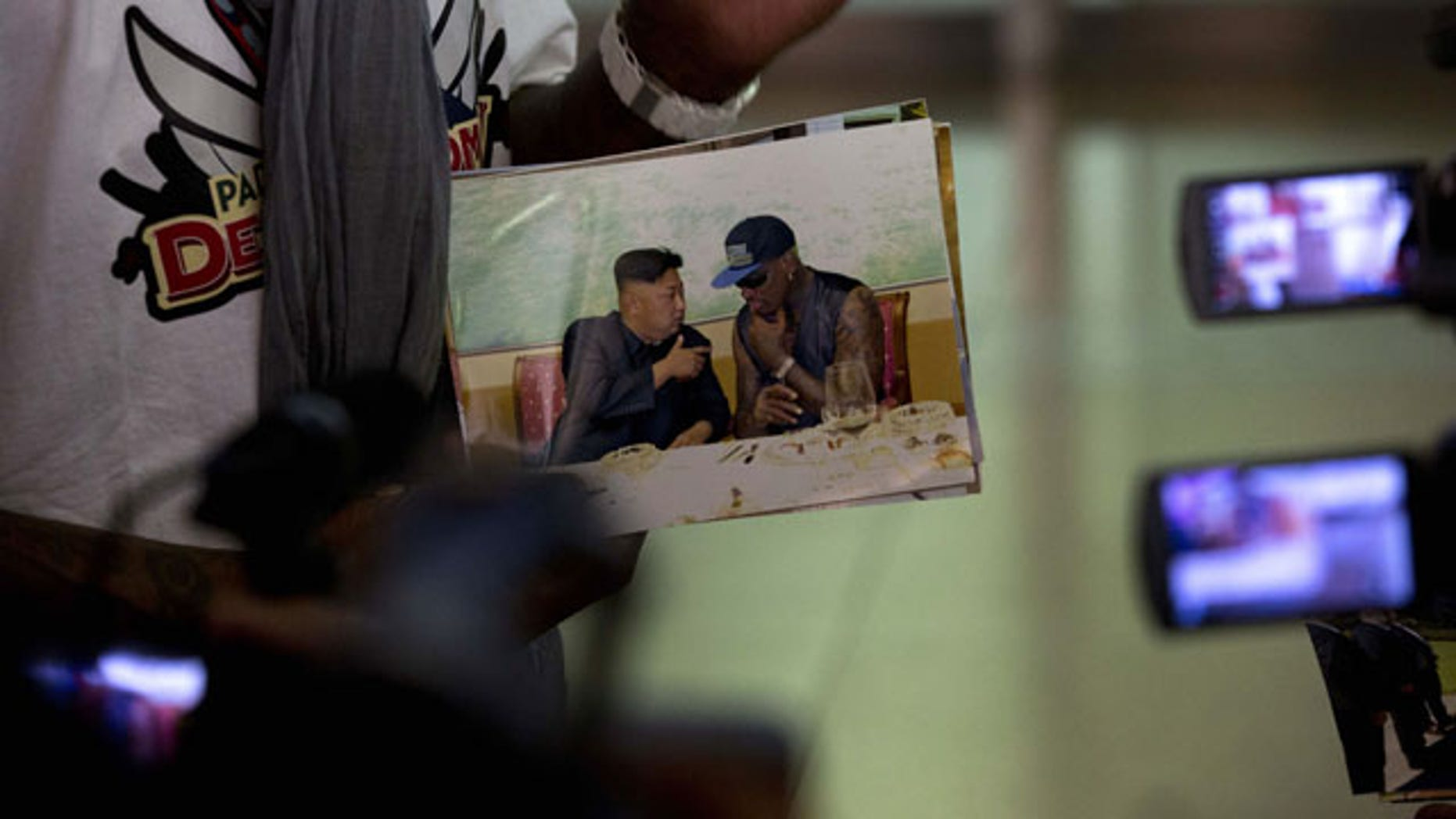September 7, 2013: Retired NBA star Dennis Rodman, left, shows a photo of him with North Korean leader Kim Jong Un upon arriving at the Beijing capital airport in Beijing, China.
