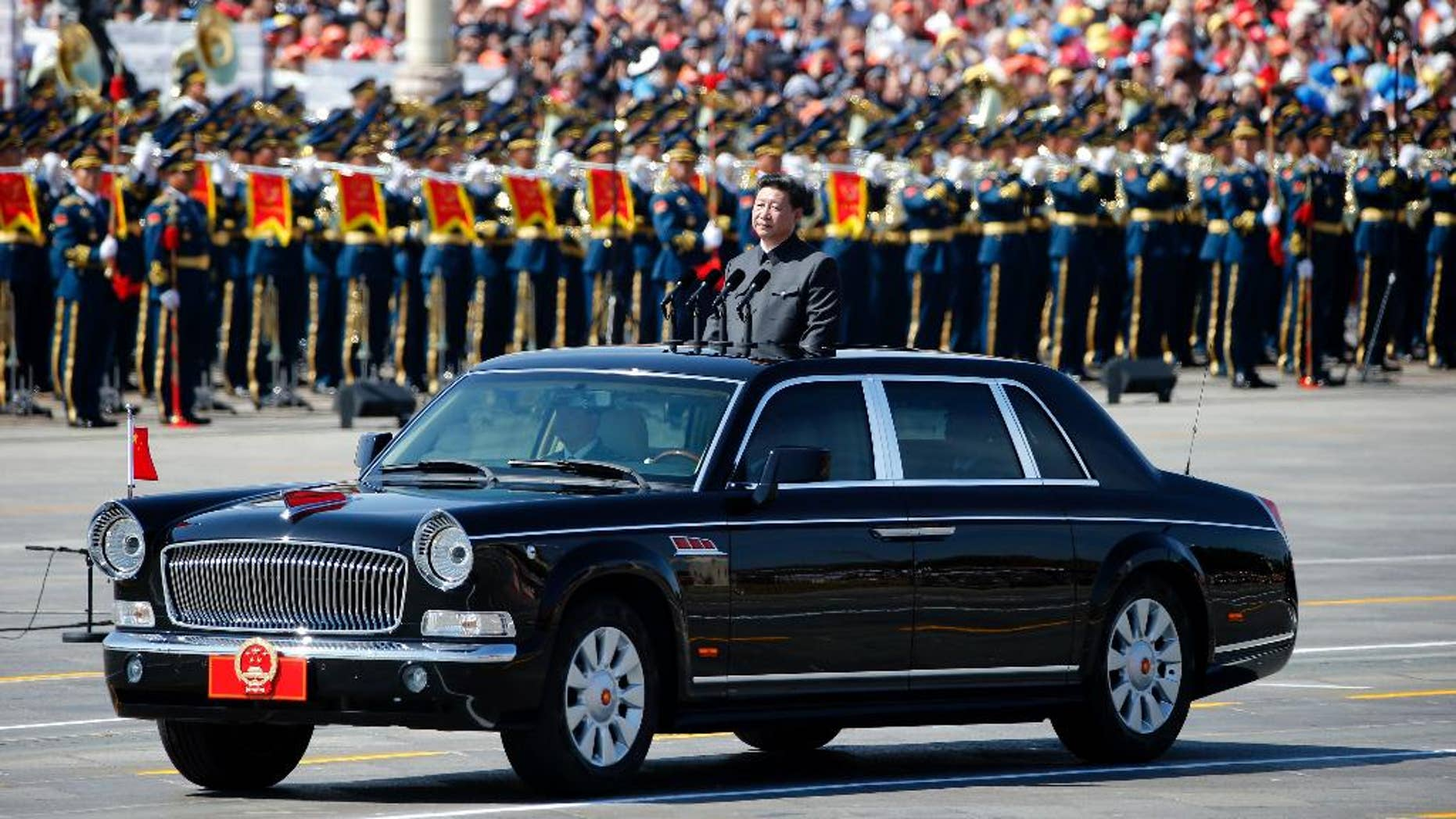 Chinese President Xi Jinping stands in a car to review the army during a parade commemorating the 70th anniversary of Japan's surrender during World War II held in front of Tiananmen Gate in Beijing, Thursday, Sept. 3, 2015. The spectacle involved more than 12,000 troops, 500 pieces of military hardware and 200 aircraft of various types, representing what military officials say is the Chinese military's most cutting-edge technology. (AP Photo/Ng Han Guan)