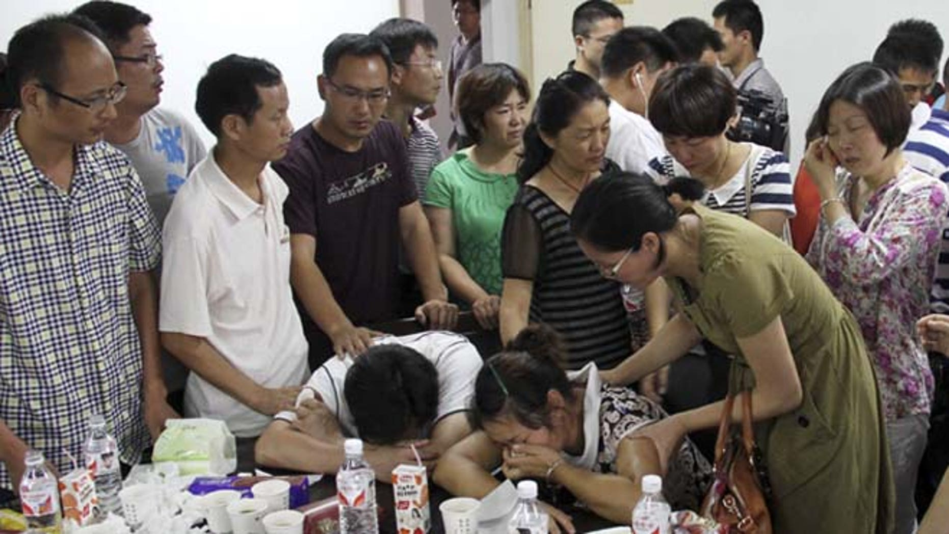 July 7, 2013: Parents of Wang Linjia, center, are comforted by parents of some other students who were on the Asiana Airlines Flight 214 that crashed at San Francisco International Airport, at Jiangshan Middle School in Jiangshan city, in eastern China's Zhejiang province. Chinese state media have identified the two people who died in the plane crash at San Francisco International Airport on Saturday as Ye Mengyuan and Wang Linjia, students at Jiangshan Middle School in China's eastern Zhejiang province.