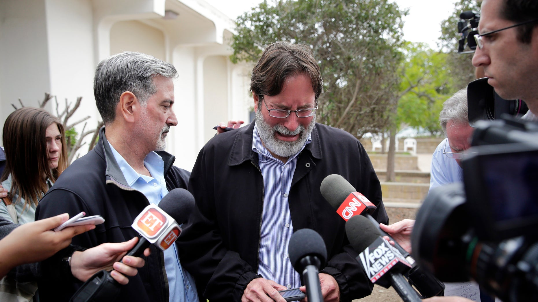 Richard Martinez is comforted by his brother Alan on Saturday, May 24, 2014, in Santa Barbara, Calif.