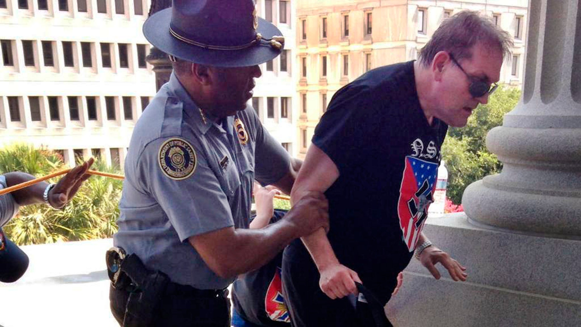 In this photo provided by Rob Godfrey, police officer Leroy Smith, left, helps a man wearing National Socialist Movement attire up the stairs during a rally Saturday, July 18, 2015, in Columbia, S.C. Members of the group were protesting Saturday the removal of the Confederate flag from the Statehouse grounds earlier this month. (Rob Godfrey via AP)