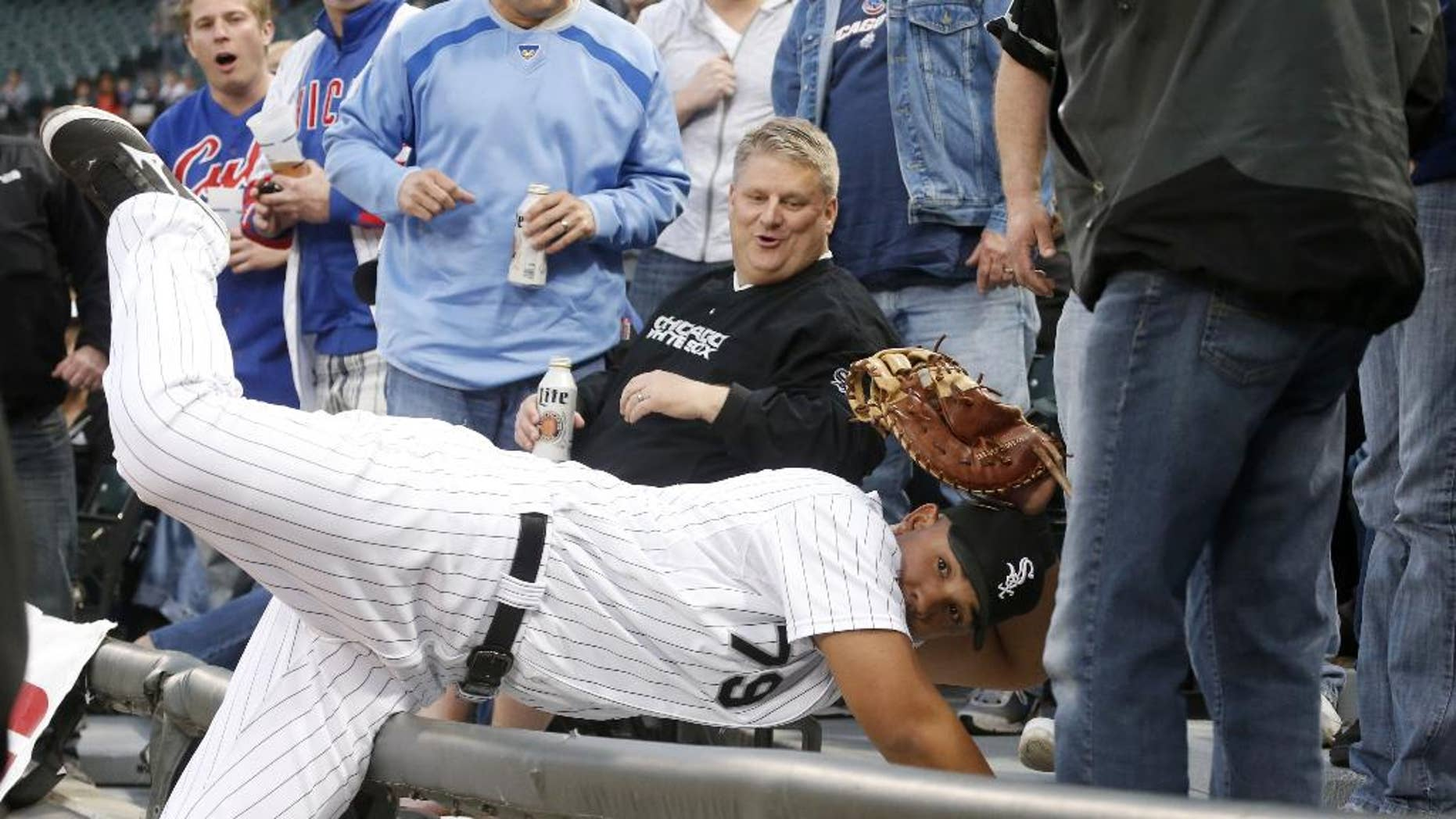 Chicago White Sox first baseman Jose Abreu shows his glove to first base umpire Marvin Hudson, after catching a fly ball off the bat of Chicago Cubs' Darwin Barney in the seats, during the second inning of an interleague baseball game Wednesday, May 7, 2014, in Chicago. (AP Photo/Charles Rex Arbogast)