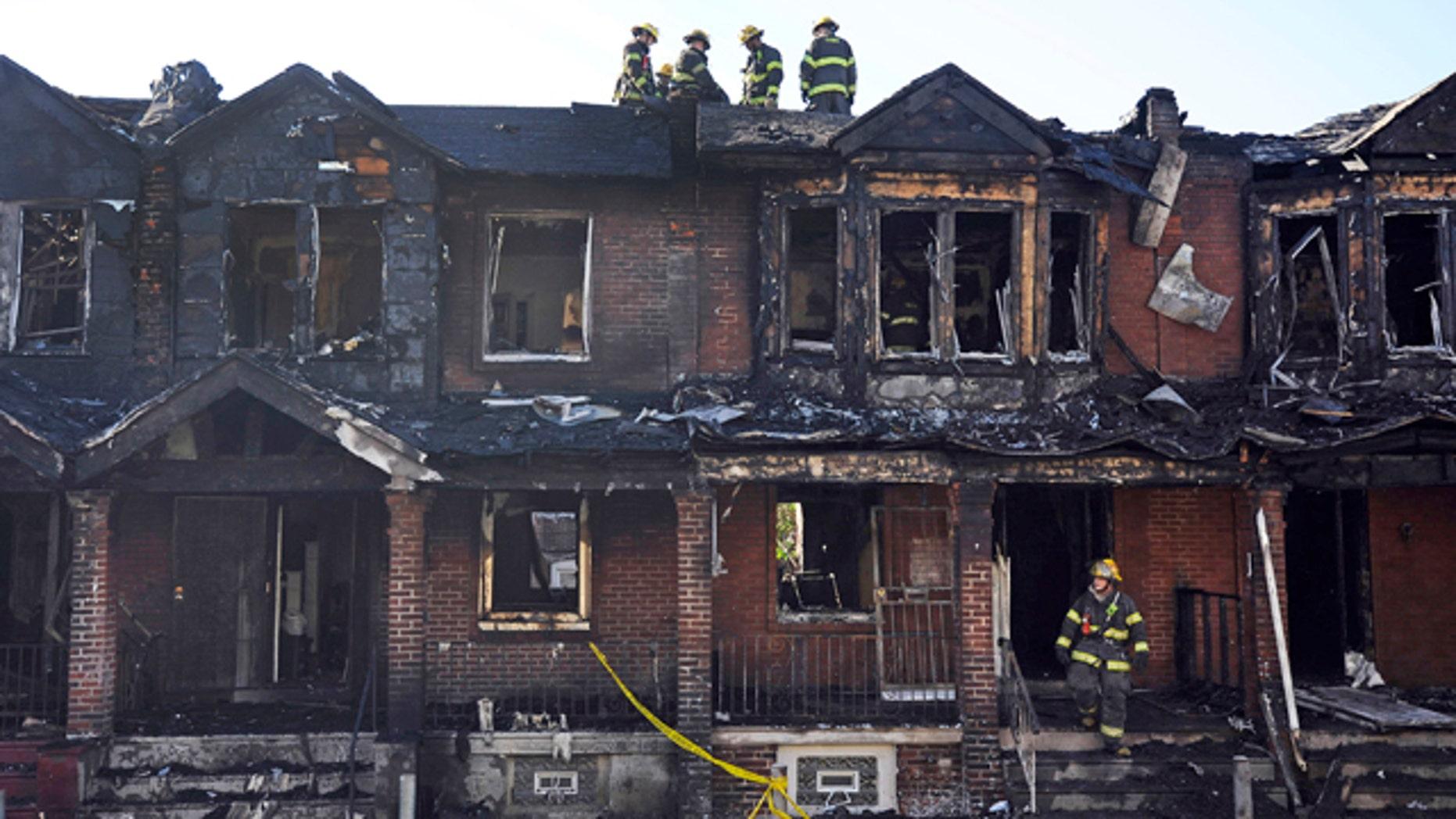 July 5, 2014: Philadelphia firefighters work on burned row homes. (AP Photo/Michael Perez)