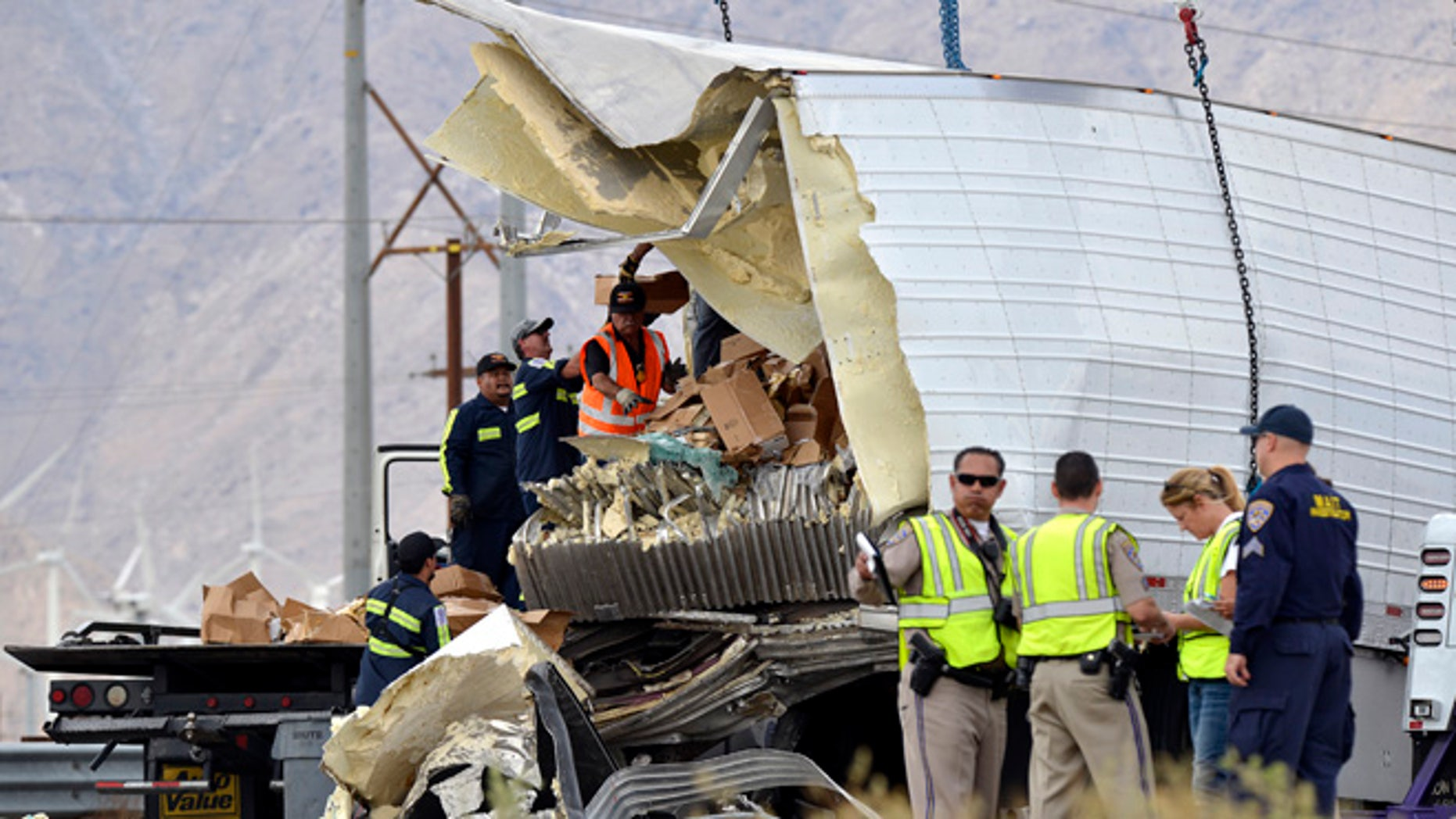 Workers remove debris from a semi-truck that crashed with a tour bus near Palm Springs, Calif., Sunday, Oct. 23, 2016.