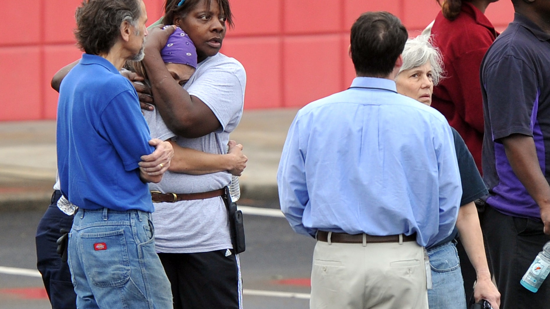 FedEx employees gather at a skating rink following a shooting at a FedEx facility in Kennesaw, Ga., on April 29, 2014.