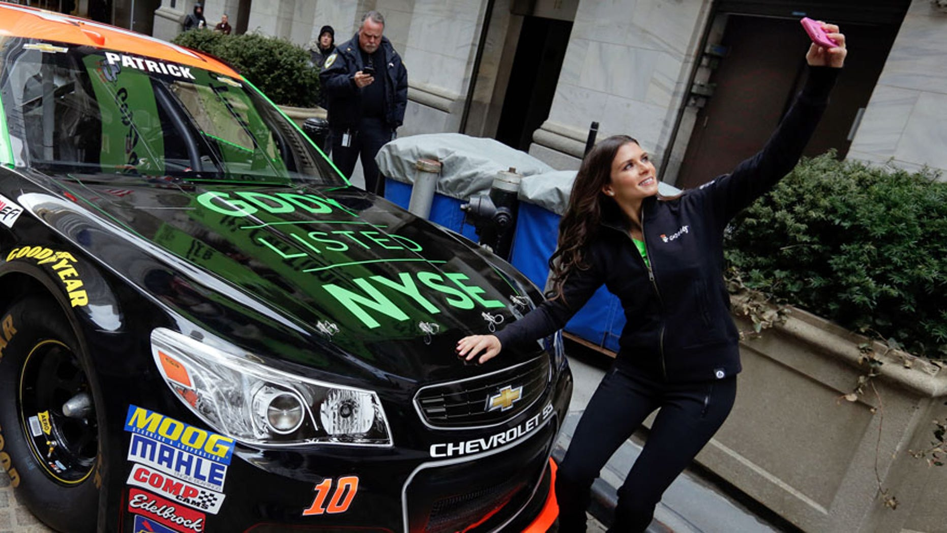 Race car driver Danica Patrick takes a selfie with her car in front of the New York Stock Exchange, before the GoDaddy IPO, Wednesday, April 1, 2015. (AP Photo/Richard Drew)