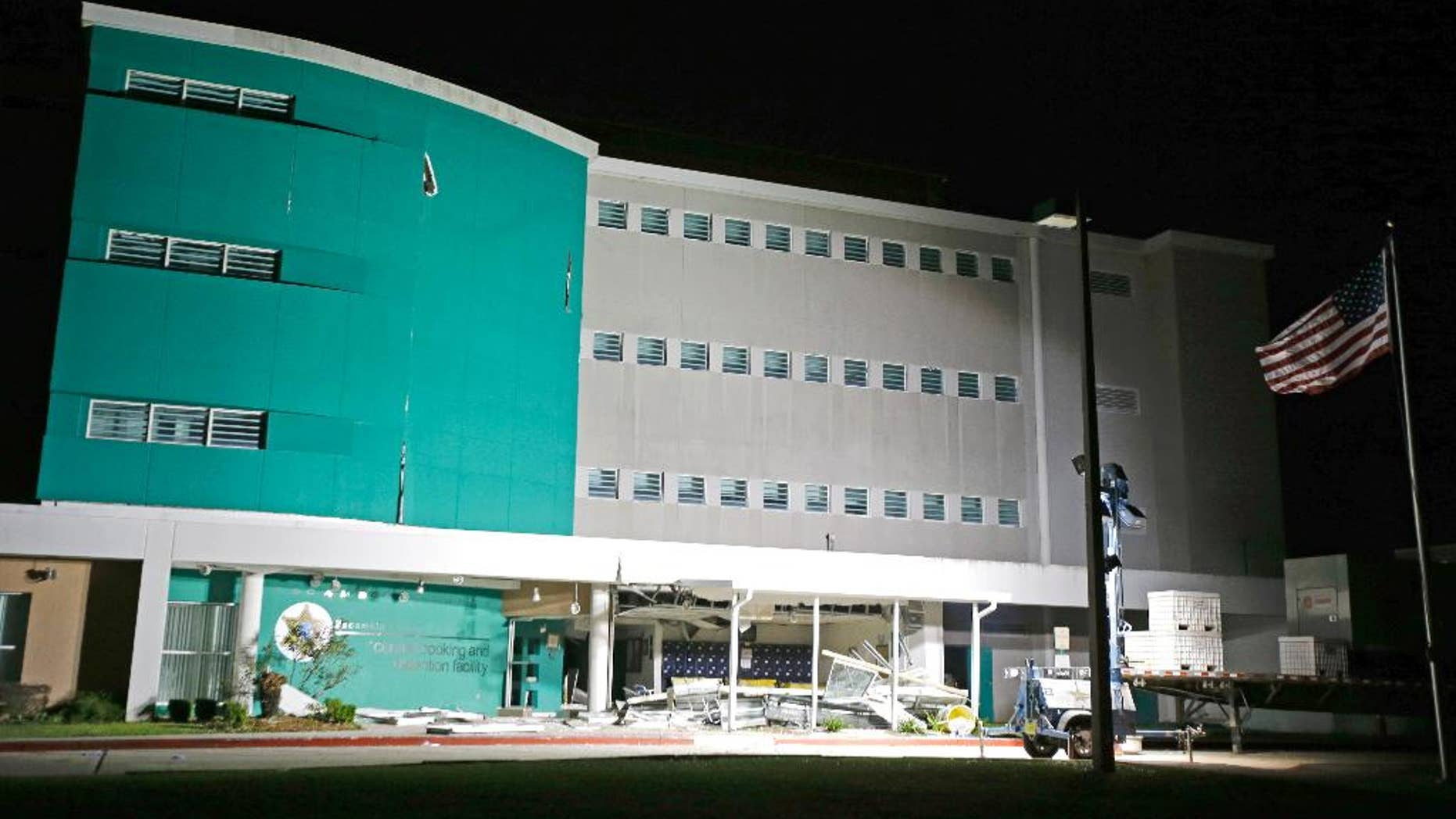 Debris from an explosion at the Escambia County Jail is scattered at the entrance to  the facility, Thursday, May 1, 2014, in Pensacola, Fla. Two inmates were killed and more than 100 others injured in the explosion according to an Escambia County spokeswoman. (AP Photo/John Raoux)