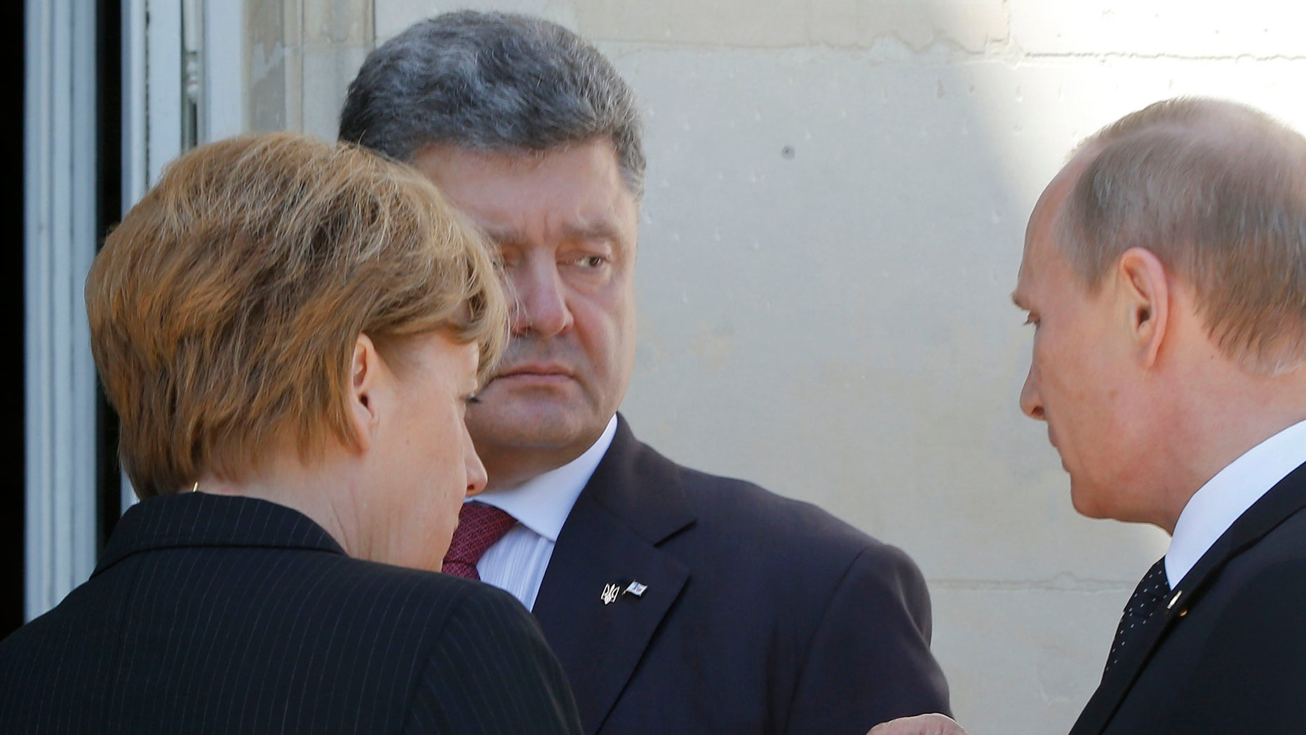June 6, 2014 - German Chancellor Angela Merkel, left, Russian President Vladimir Putin, right, and Ukrainian president-elect Petro Poroshenko, center, talk after a group photo before a luncheon as they take part in the 70th anniversary of D-Day in Benouville in Normandy, France.