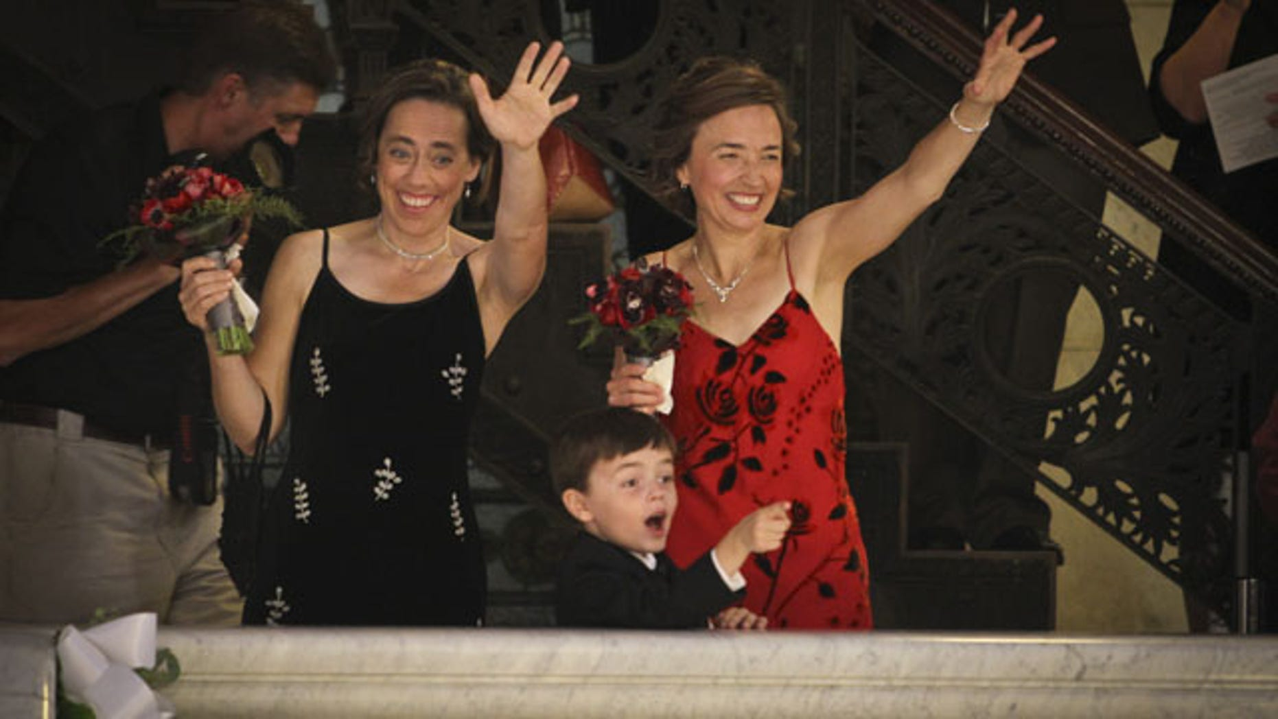 August 1, 2013: Margaret Miles, black dress, left, and Cathy ten Broeke, right, were the first same-sex couple to be married by Mayor R.T. Rybak at midnight at Minneapolis City Hall. Their son, Louie Miles ten Broeke, 5, center, was also present. (AP Photo)