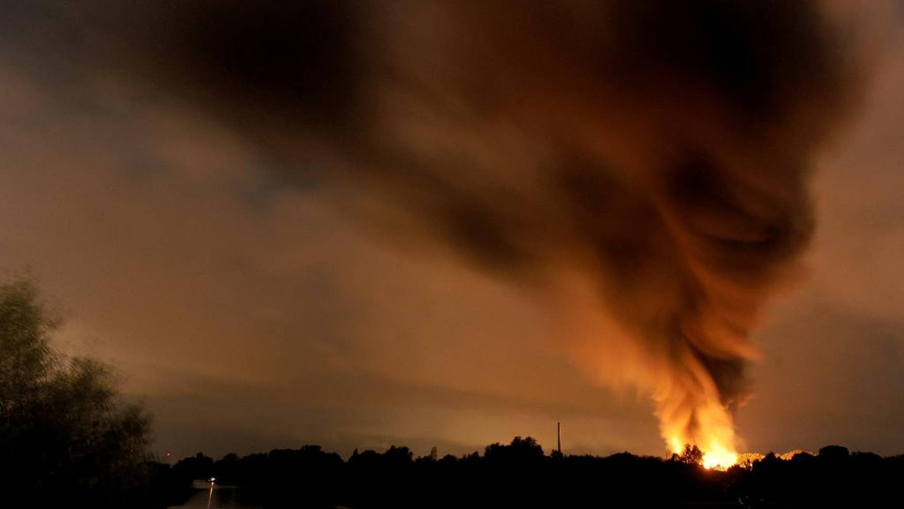 Smoke and flames rise over a chemical waste facility in Ritterhude near Bremen, Tuesday evening, Sept. 9, 2014.  Police said that one person was severely burned in the blast Tuesday night and that the explosion damaged a nearby residential area.  (AP Photo/dpa, Ingo Wagner)