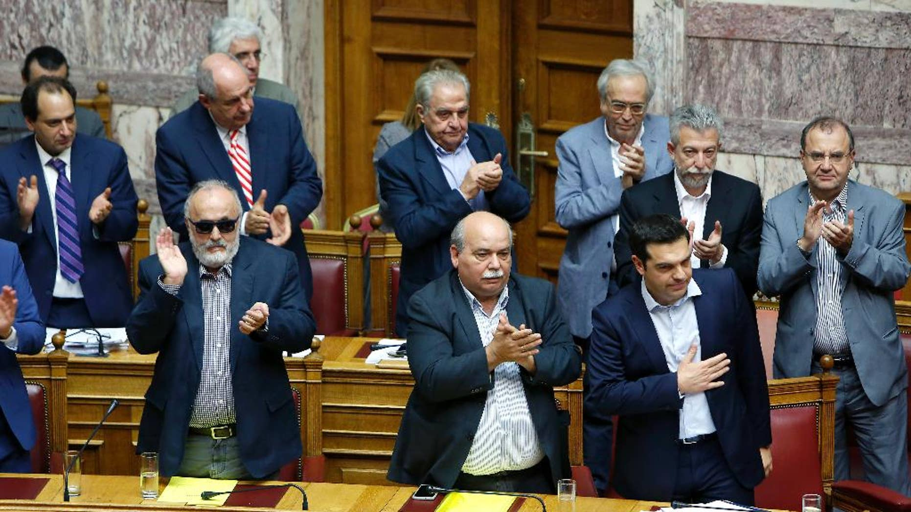 Ministers of Greek government applaud the  Greece's Prime Minister Alexis Tsipras after his speech in an emergency Parliament session for the government's proposed referendum in Athens, Saturday, June 27, 2015. Greece's place in the euro currency bloc looked increasingly shaky on Saturday, when eurozone countries rejected a monthlong extension to its bailout program and the prime minister called for a risky popular vote on the country's financial future. (AP Photo/Petros Karadjias)