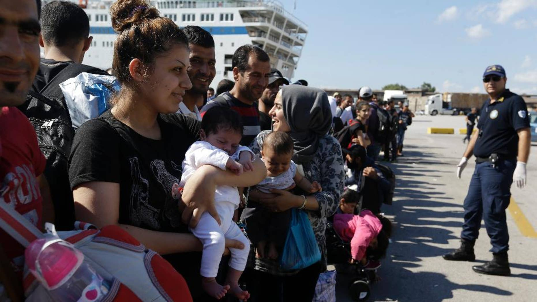 A Syrian mother, left, holds her one-month old daughter as she waits for the bus transporting them to the metro station after their arrival from the Greek island of Lesbos at the Athens' port of Piraeus, Monday, Sept. 28, 2015. The Greek ferry Elefhterios Venizelos is part of special ferry service for refugees and migrants that carries 2,500 paying passengers. More than 250,000 asylum seekers have passed through Greece so far this year. (AP Photo/Thanassis Stavrakis)