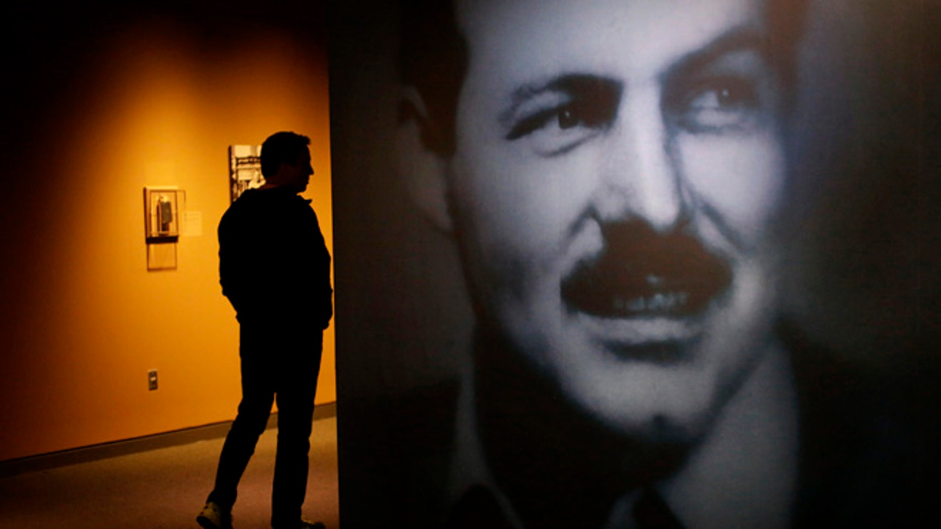 "A museum visitor, left, walks past a photograph of Ernest Hemingway in the exhibit: ""Ernest Hemingway: Between Two Wars"" at the John F. Kennedy Presidential Library and Museum on Tuesday, April 12, 2016, in Boston. Original drafts of Ernest Hemingway works along with personal items are on display for the first time at the museum. (AP Photo/Steven Senne)"