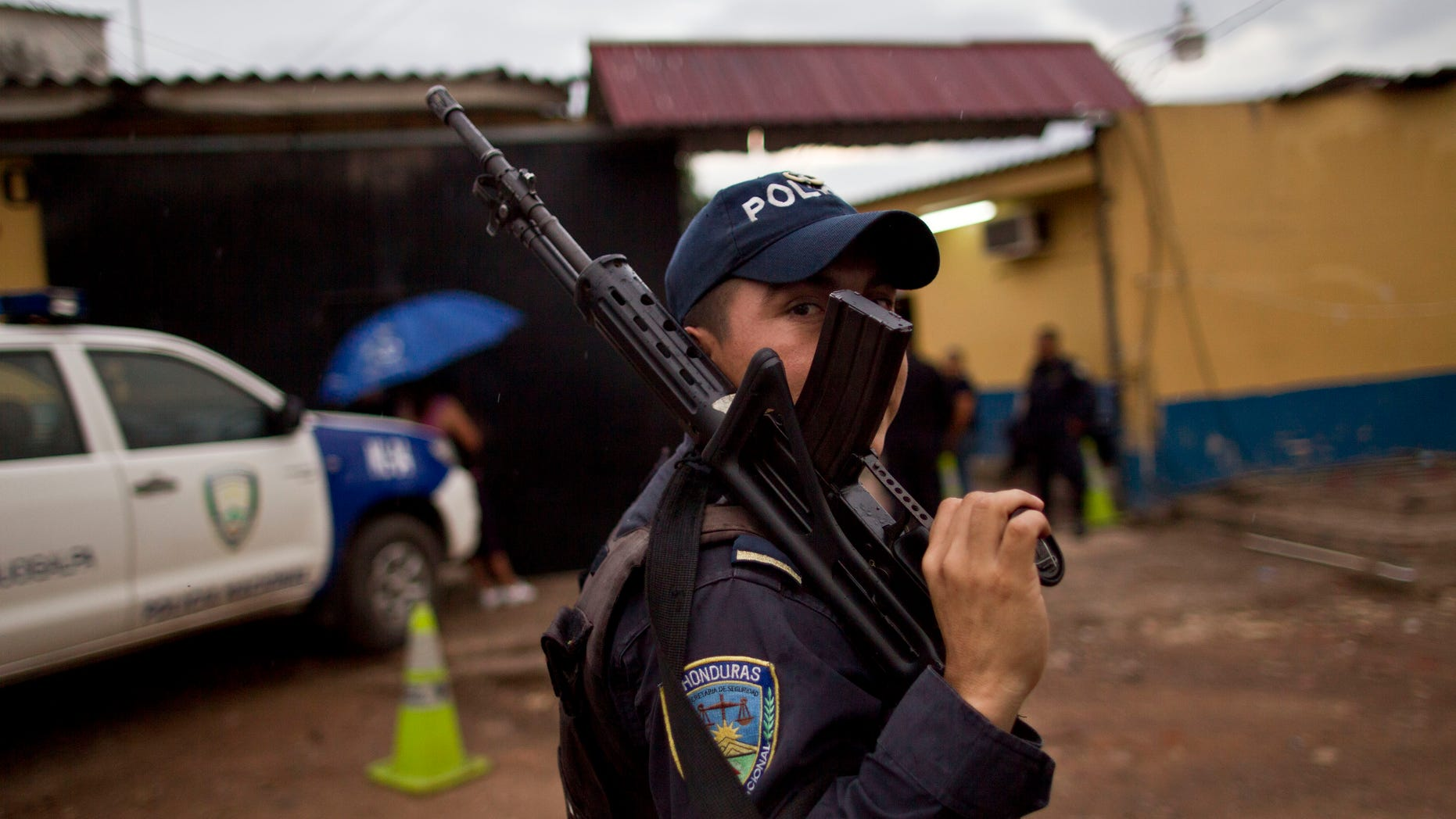 In this June 1, 2013 photo, a National Police officer looks from behind his weapon during an operative outside a police station near El Mayoreo markert in Tegucigalpa, Honduras. The government of Honduras launched an unprecedented effort last year to clean up a U.S.-backed police force widely seen as deeply brutal and corrupt. One by one, hundreds of police officers were subjected to polygraph tests administered by Colombian technicians funded by the U.S. government. Nearly four of every 10 officers failed the test in the first five months it was administered, some giving answers that indicated that they had, among other violations, tortured suspects, accepted bribes and taken drugs, according to a confidential U.S. document provided to The Associated Press. (AP Photo/Esteban Felix)