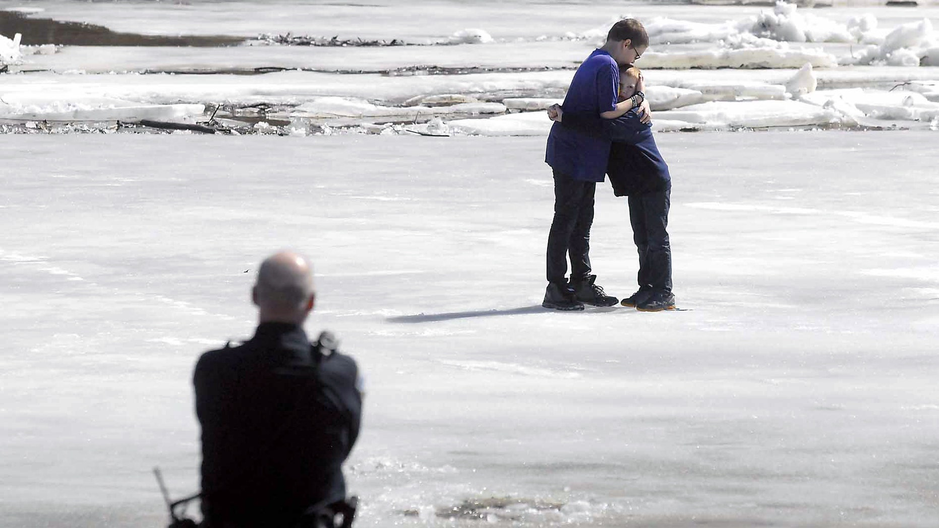 March 20, 2014: In this photo, Corbin Crawford, 12, left, holds his brother, Dylan Crawford, 7, as the pair await rescue from the shifting ice above the Hydroelectric Dam on the Des Moines River near Fort Dodge, Iowa.
