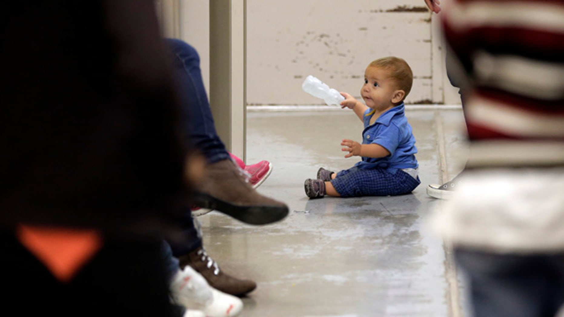 June 18, 2014: A toddler sits on the floor with other detainees at a U.S. Customs and Border Protection processing facility in Brownsville,Texas. (AP Photo/Eric Gay, Pool)